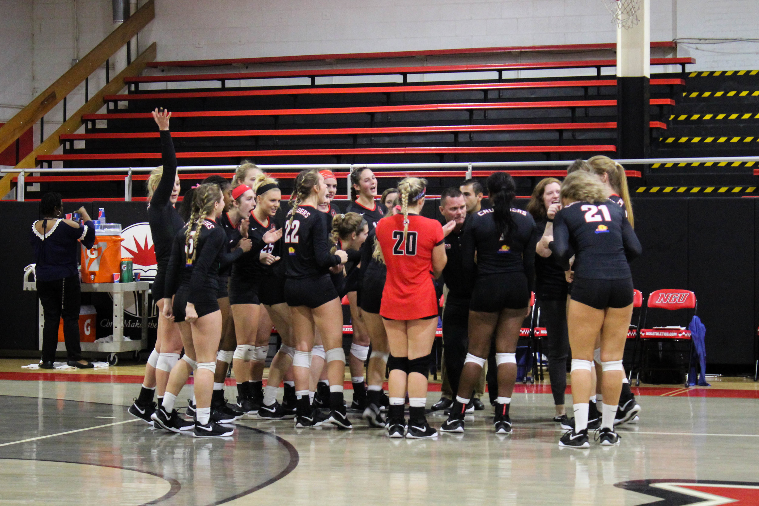 After winning a set, the NGU women's volleyball team huddle together to cheer on the players that were on the court.