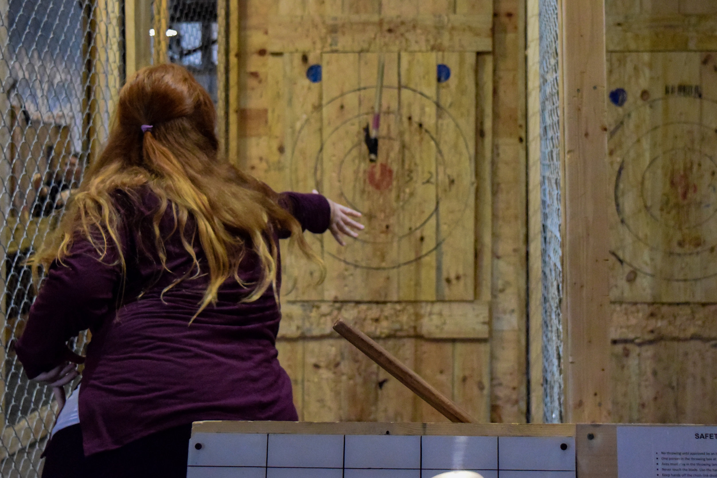 Junior Julie Nalley brings her arms back to throw the axe toward the target.