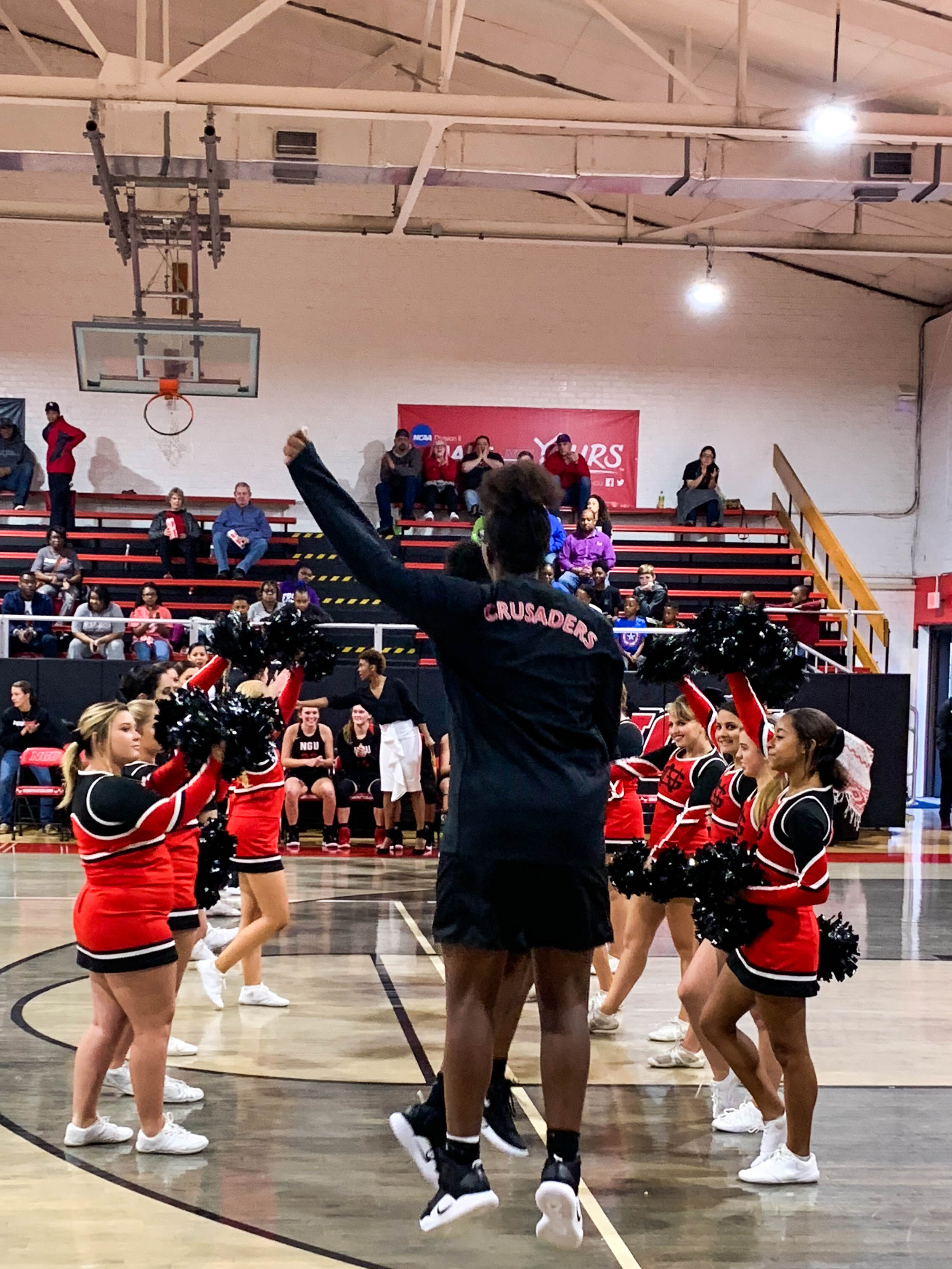Freshman Asia Jones (24) chest bumps the starters for NGU as their names are called at the start of the game.