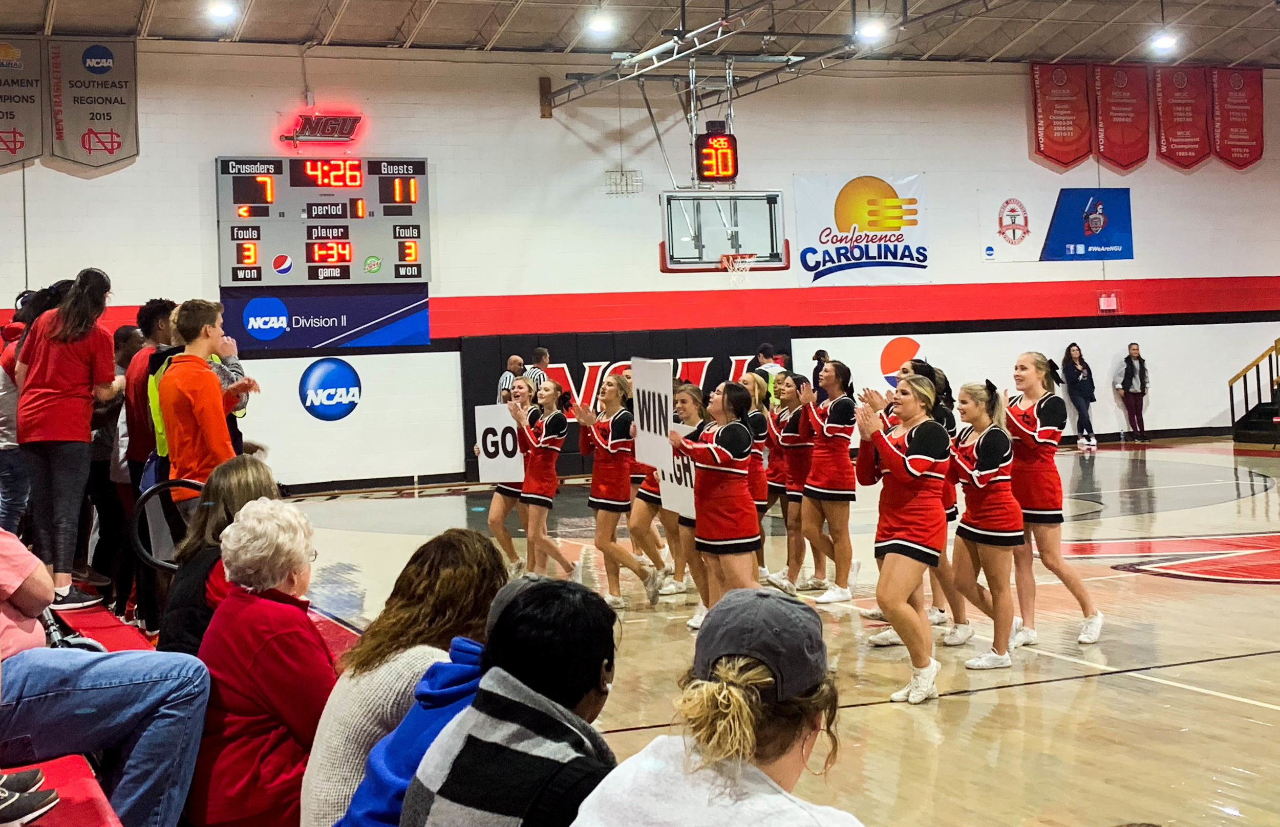 During a time out, the NGU cheerleaders take the court in front of the student section to lead them in a cheer.