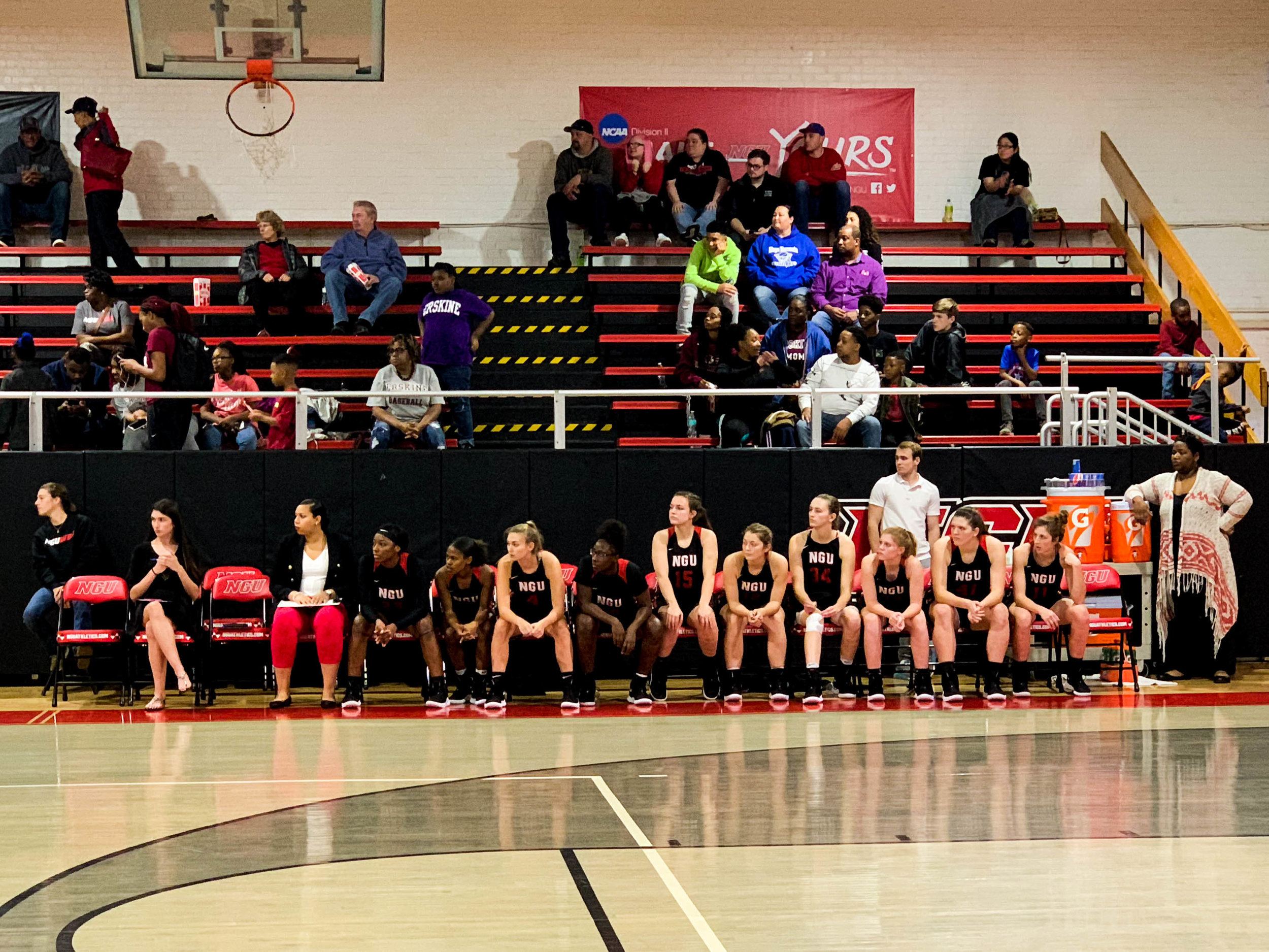 The NGU team watches as its teammates play.