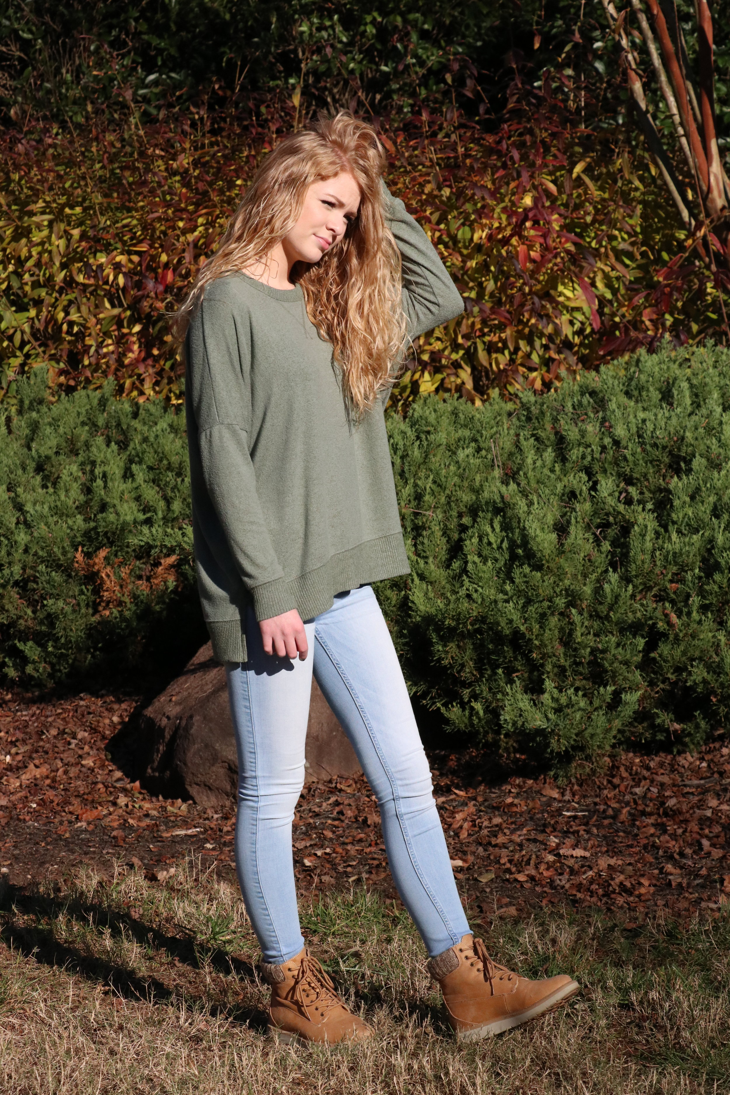 Taylor Loughry, Sophomore, goes with a green loose sweater over light washed jeans and some light brown combat boots.