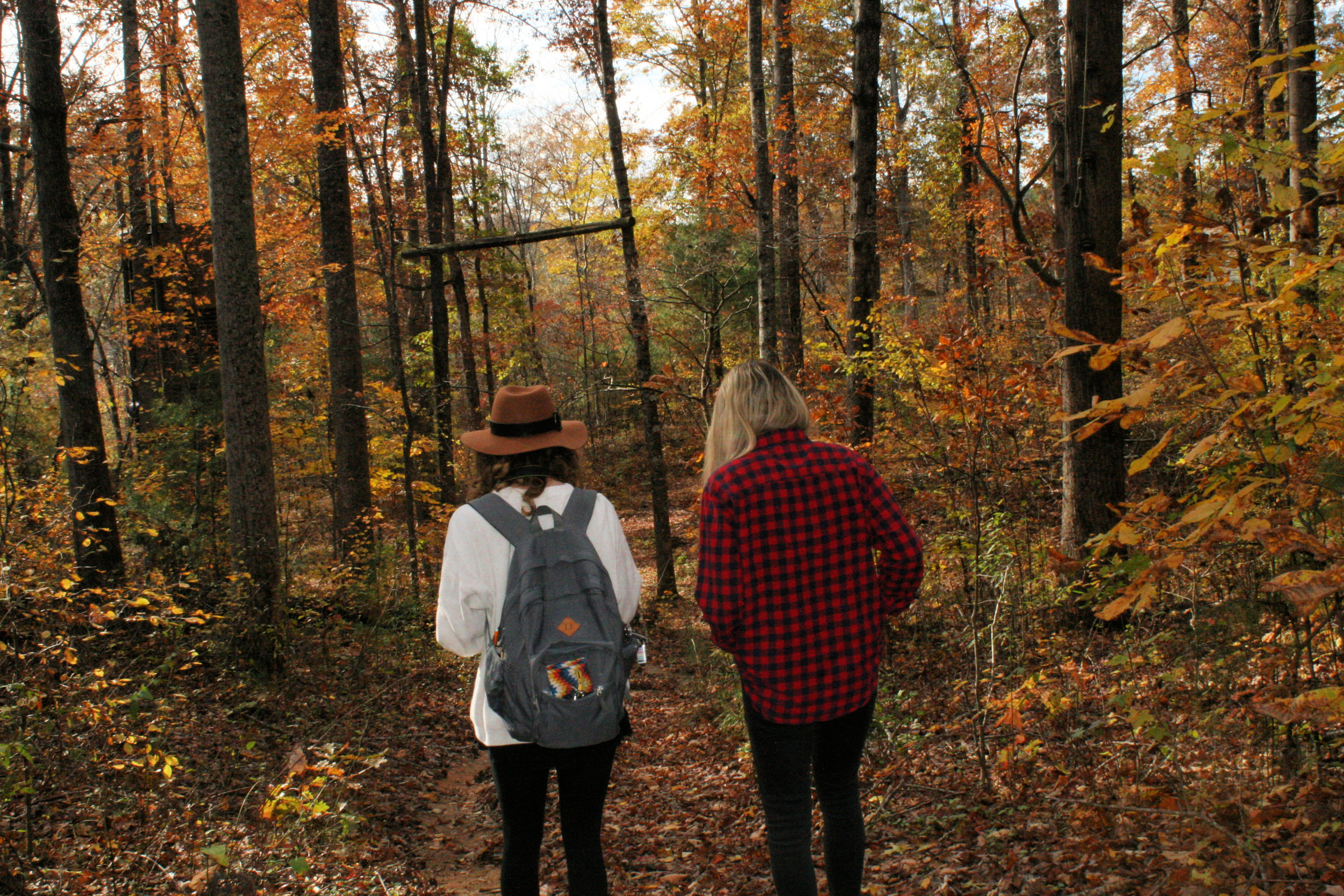 Sophomores, Courtney Chestnut and Katelyn Benfield hike through the woods at North Greenville University to look for a spot to shoot.