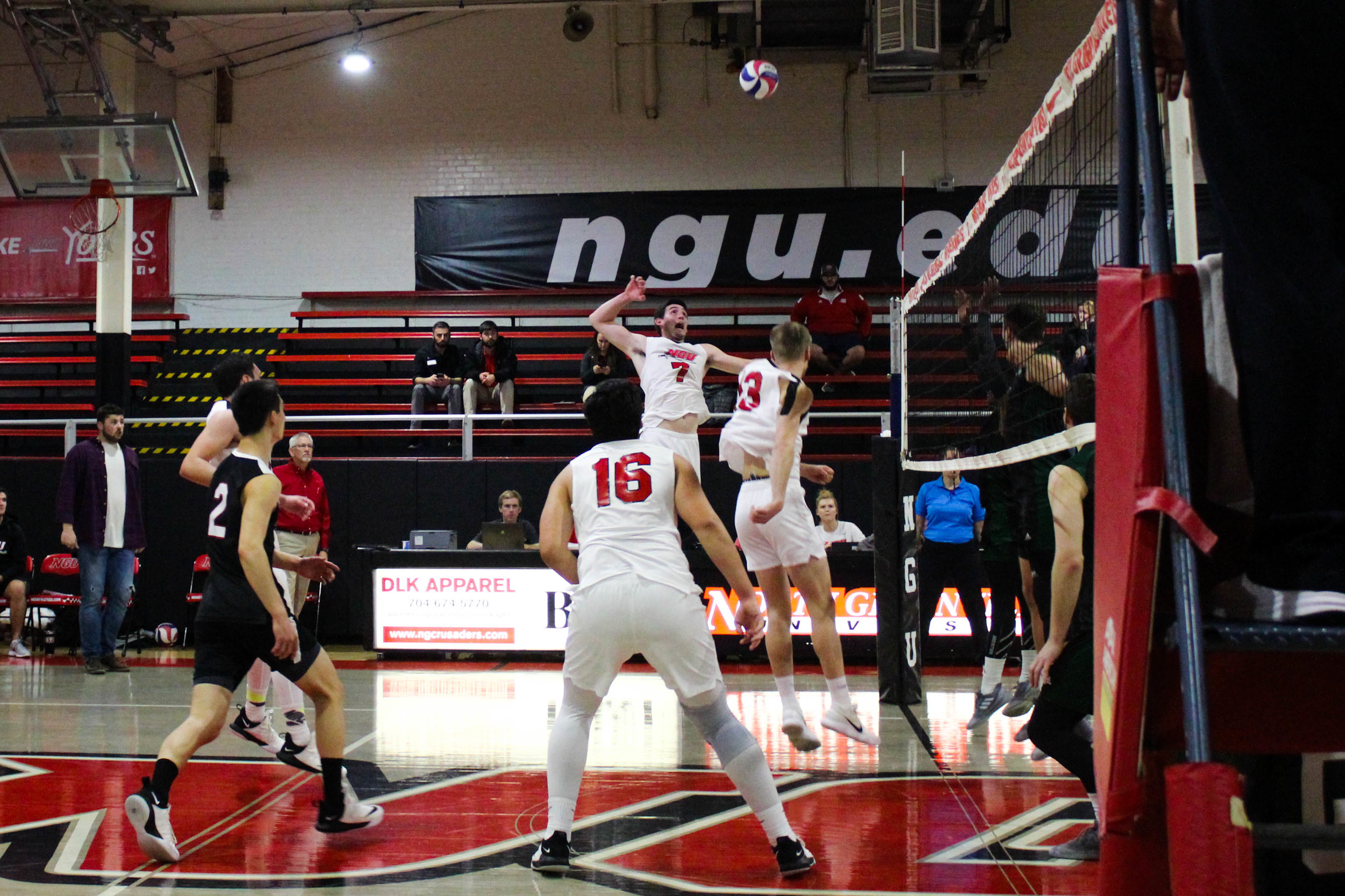 Junior Jackson Gilbert (7) leaps to spike the ball over the net onto Mount Olive's side.