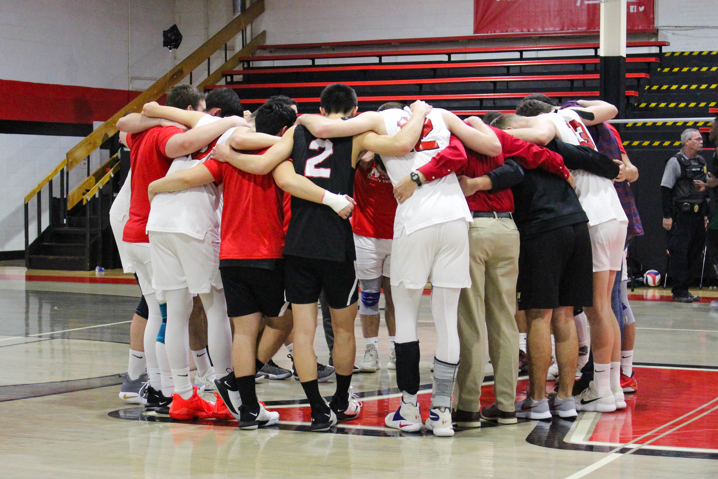 The Crusader men's volleyball team huddle together to pray after the game.