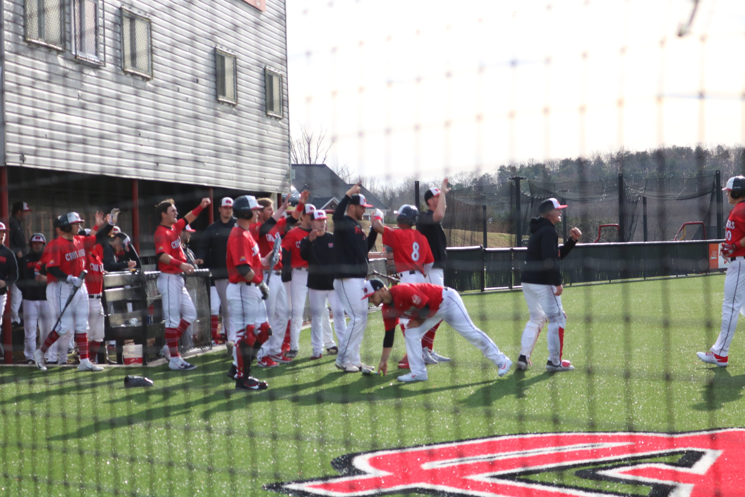 The Crusaders high five Whitehead (8) as he heads in from home plate, scoring the first point of the season.
