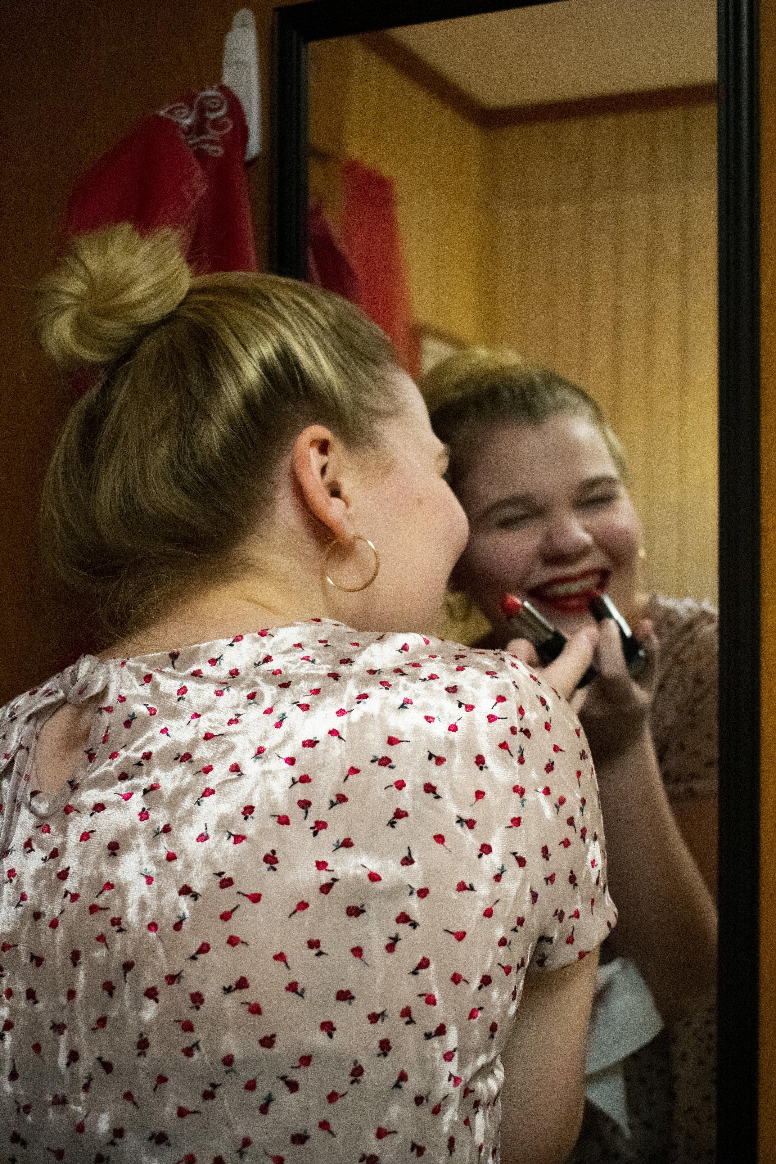 Freshman Emily Hansen wants to feel festive so she carefully applies red lipstick.