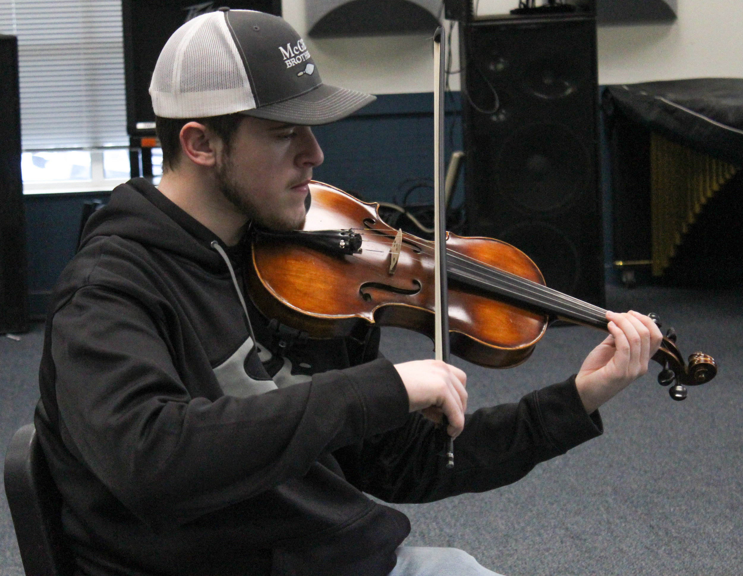 Brandon McAlister plays along with the orchestra using the violin.