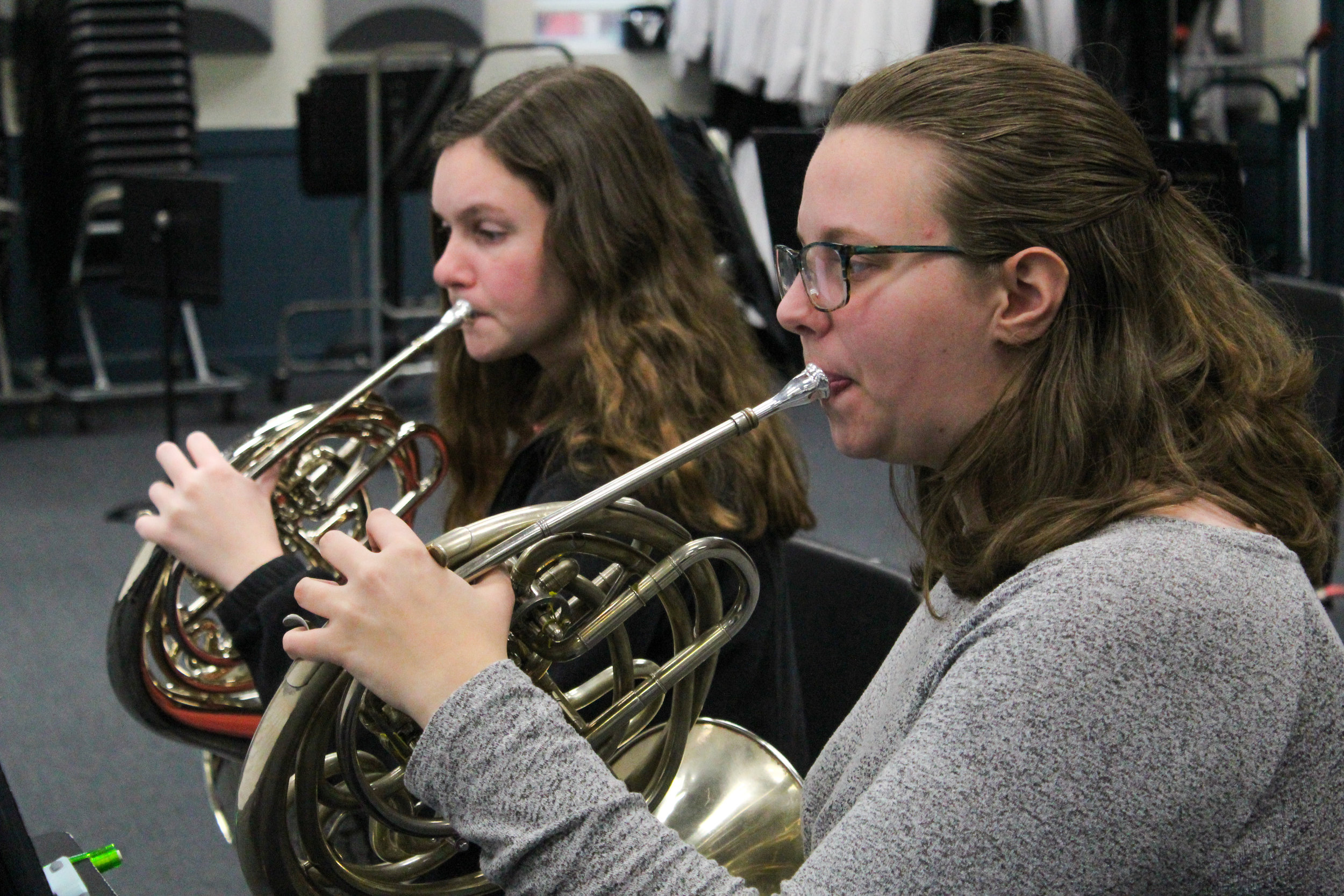 The two orchestra students practice playing their horns.