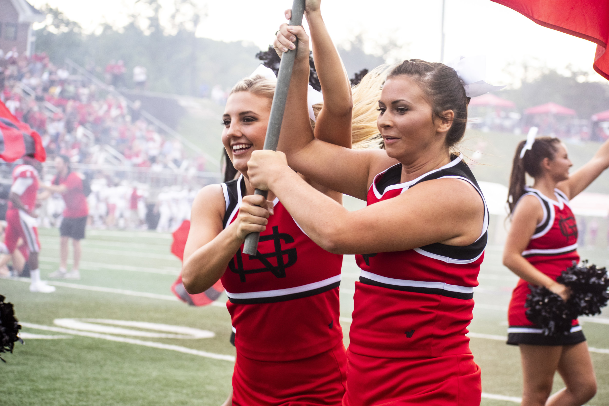 Junior Caitlin Frederiksen and Sophomore Faith Therrell start the game by running down the field with a flag.