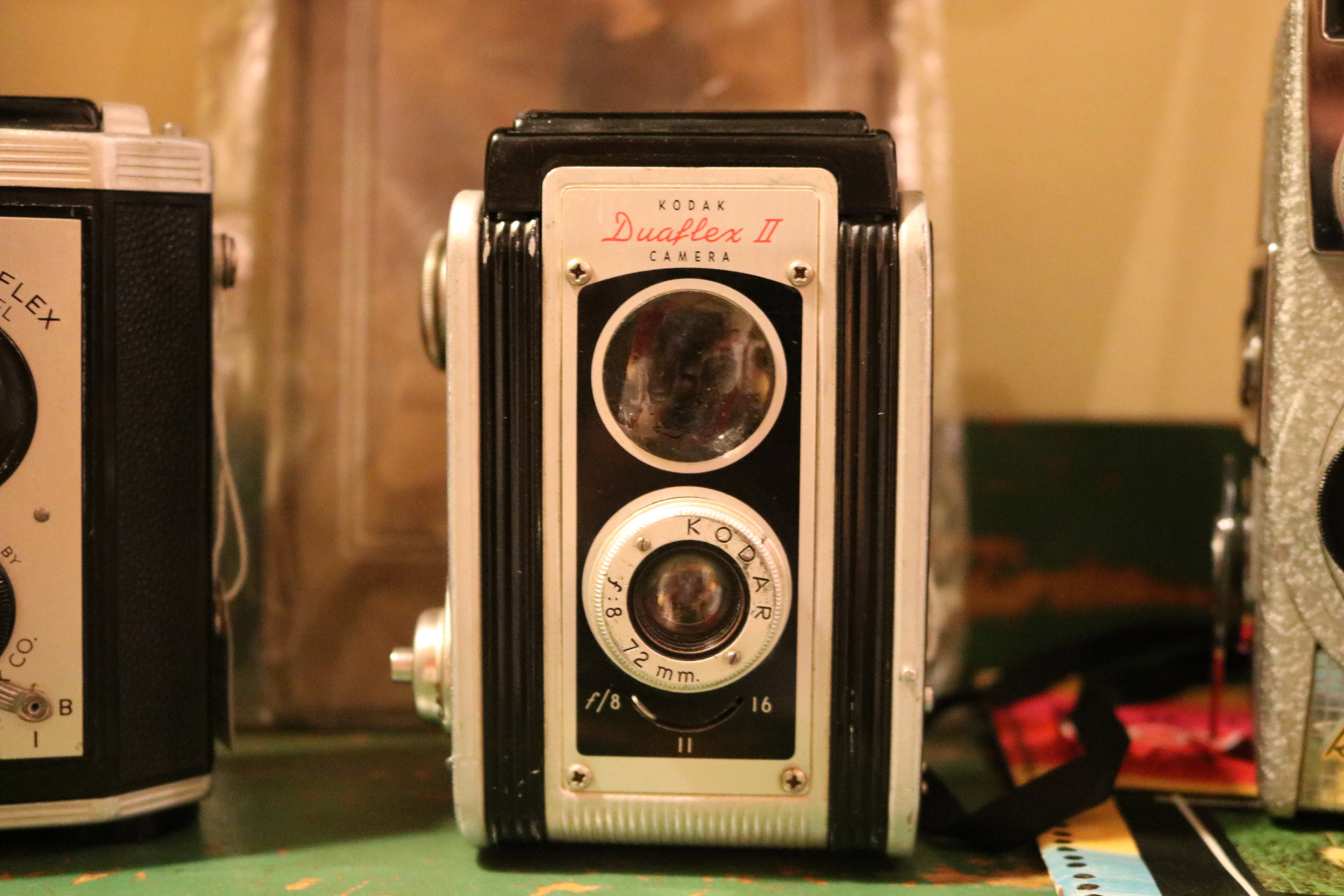 A Kodak Duaflex II camera for sale in the collection of cameras throughout the store.
