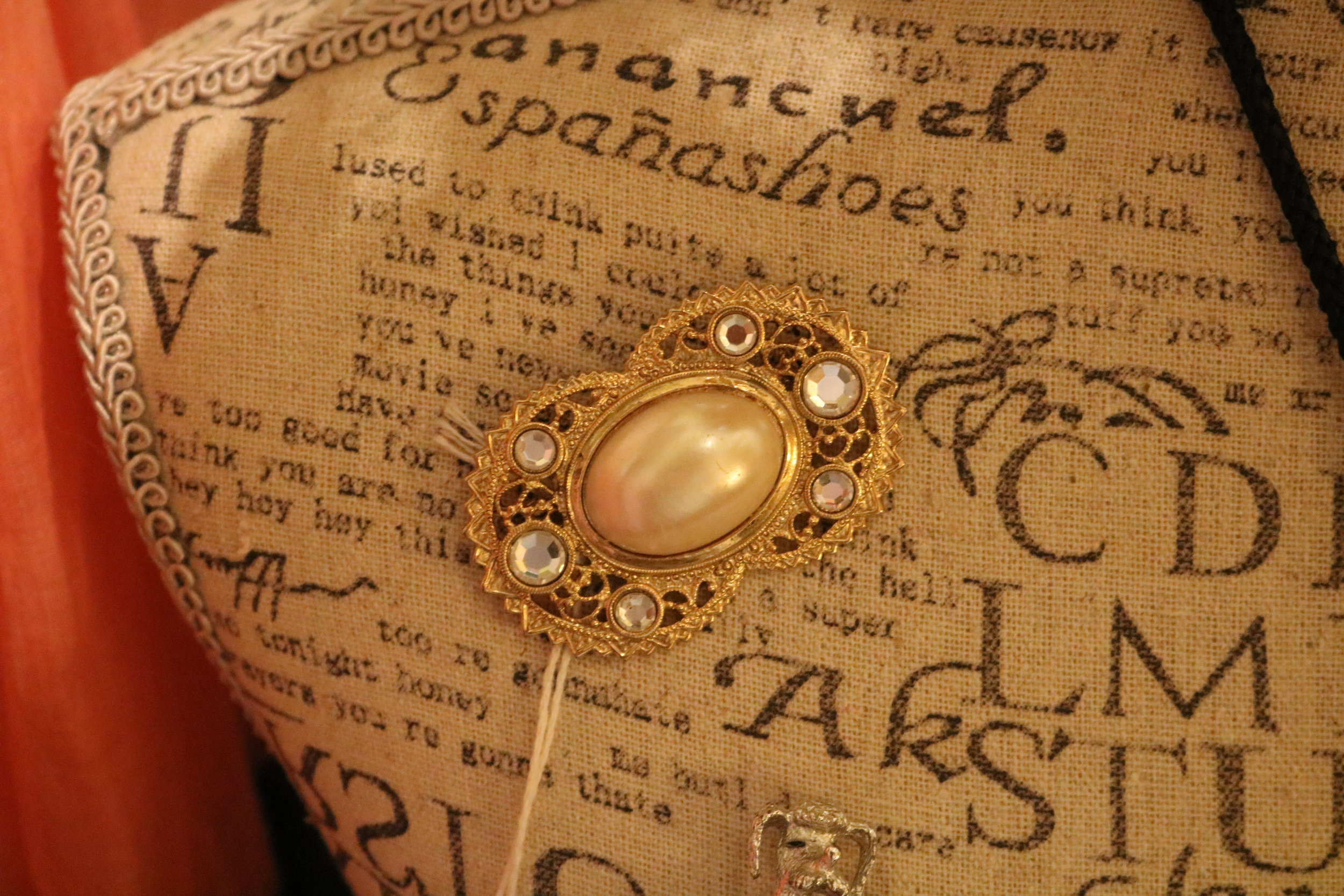 A gold and pearl broach pinned on a mannequin.