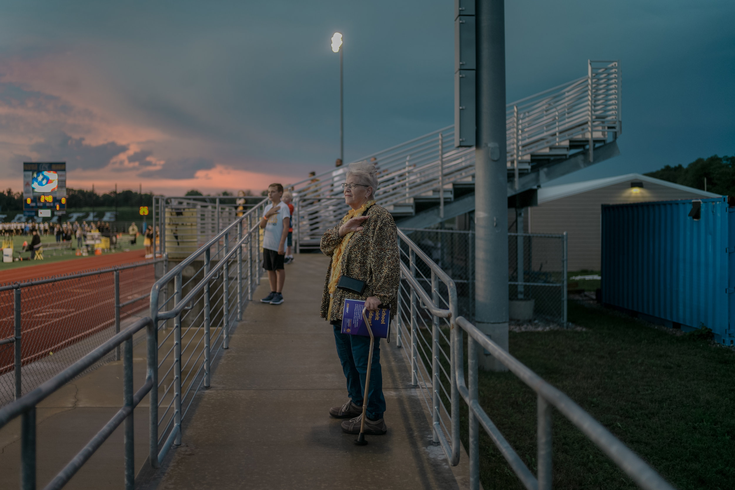 Janis Green holds her hand on her heart as the Muriel Battle High School band plays the National Anthem at a game against Smith-Cotton High School on Friday, August 31, 2018 at Battle. Green, a 1964 alumnus of Smith-Cotton, says she came to watch her grandson, Nate McFail, who is a safety for Smith-Cotton.