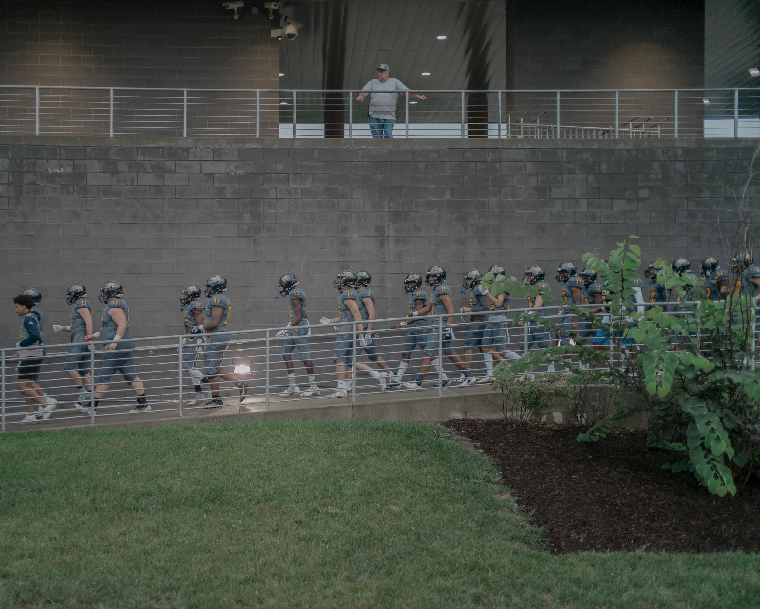 """Muriel Battle High School's football team walks into its stadium to face rival Rock Bridge High School on Friday at Battle. The team entered as Archie Eversole's """"We Ready"""" blasted through the stadium's speakers."""