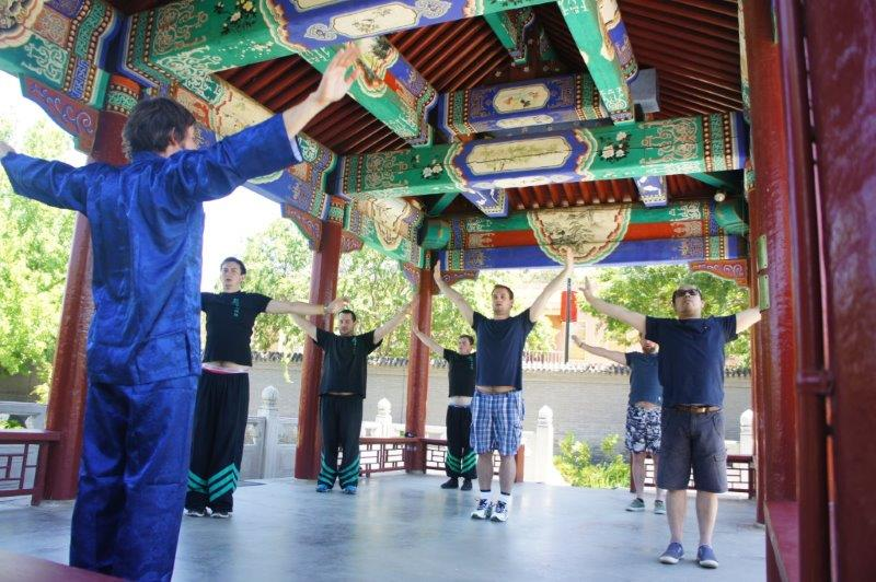 Students practicing Lifting the Sky, under the pavilion in the beautiful and tranquilHappy Garden at the Museum