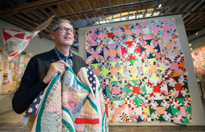Renowned quilt authority and collector Roderick Kiracofe hangs some quilts Wednesday as part of an exhibit at the Sonoma Valley Museum of Art. Image: Robbi Pengelly of Sonoma Index-Tribune.