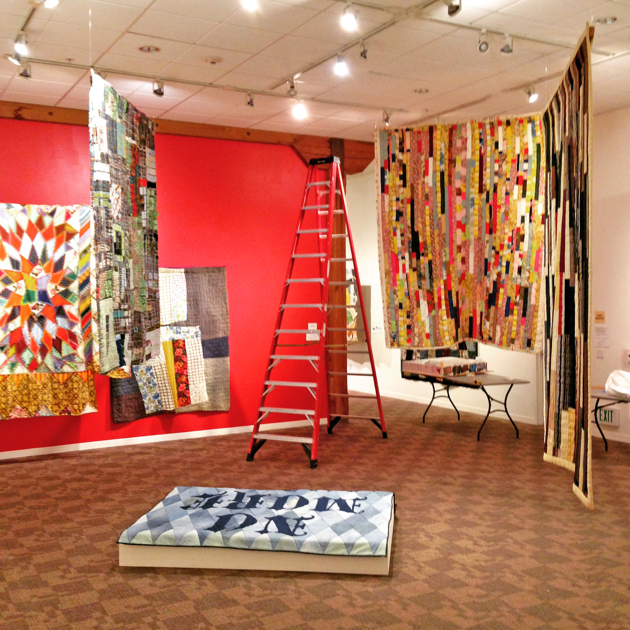 This installation allows viewers to see the front and back of many quilts.