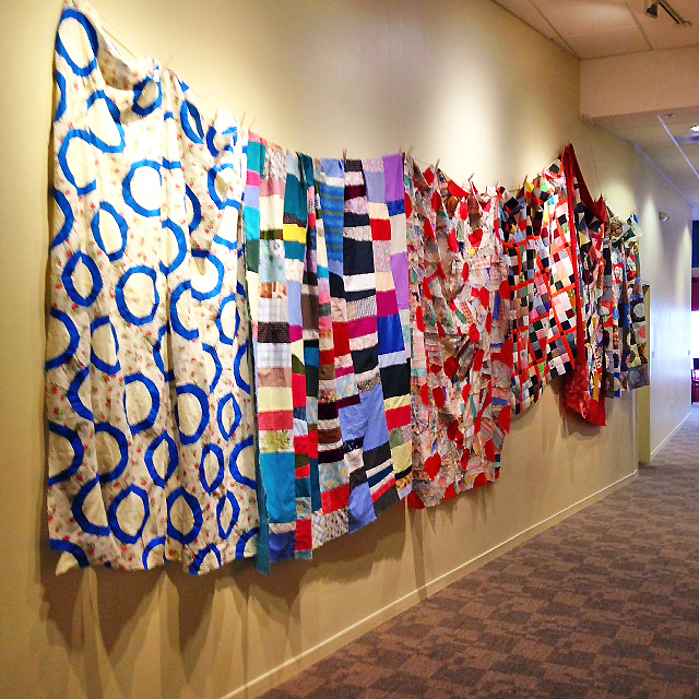 A wall of quilt tops