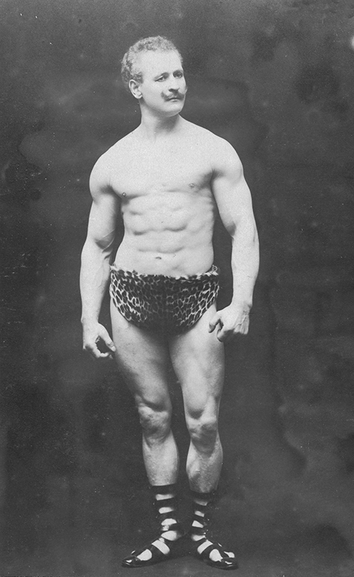 "The author has neglected to mention the limited-edition stereoscope adventure released in the late 1960s where the Doctor underwent hypnosis and recalled a past incarnation, the memory of whom he had suppressed—and not just because he realised leopard skin underpants weren't actually ""cool"". [Eugene Sandow], photograph by Henry Goldman, 1902, State Library of Victoria, H96.160/715."