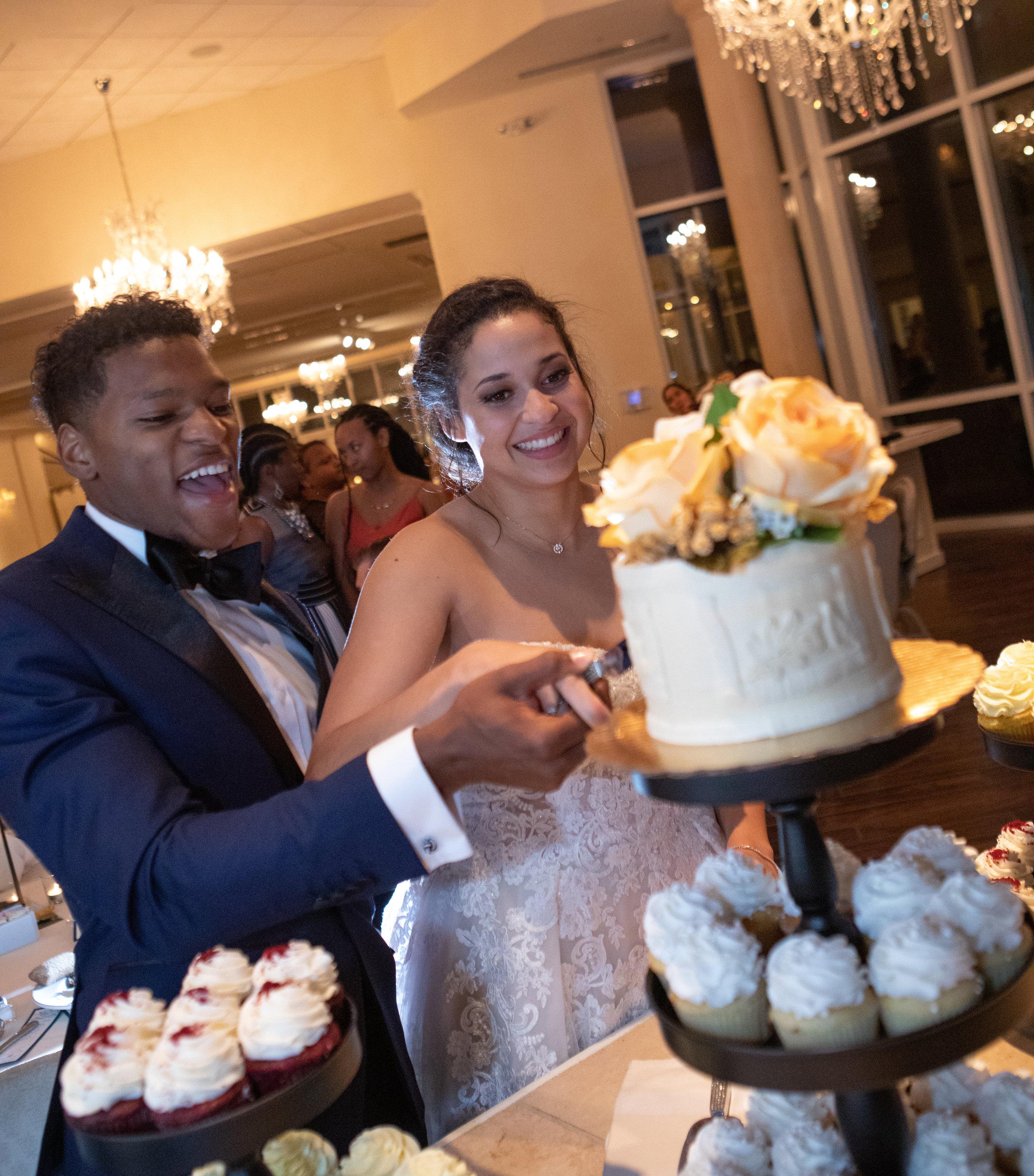 Cutting of the wedding cake photo by the Atlanta Wedding Photographers at AtlantaArtisticWeddings