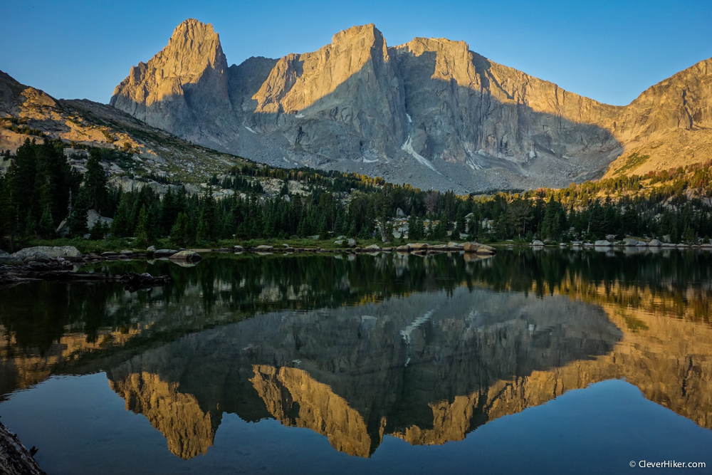 War Bonnet Peak and Warrior Peaks reflect in Lonesome Lake as morning wakes.