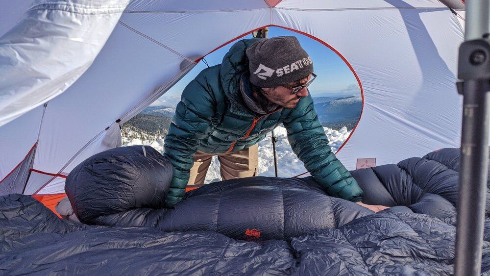 A hiker situating a sleeping bag in a 4-season tent on a winter camping trip.