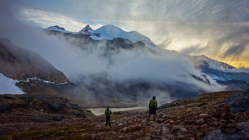 Two backpackers standing in front of a foggy mountain view