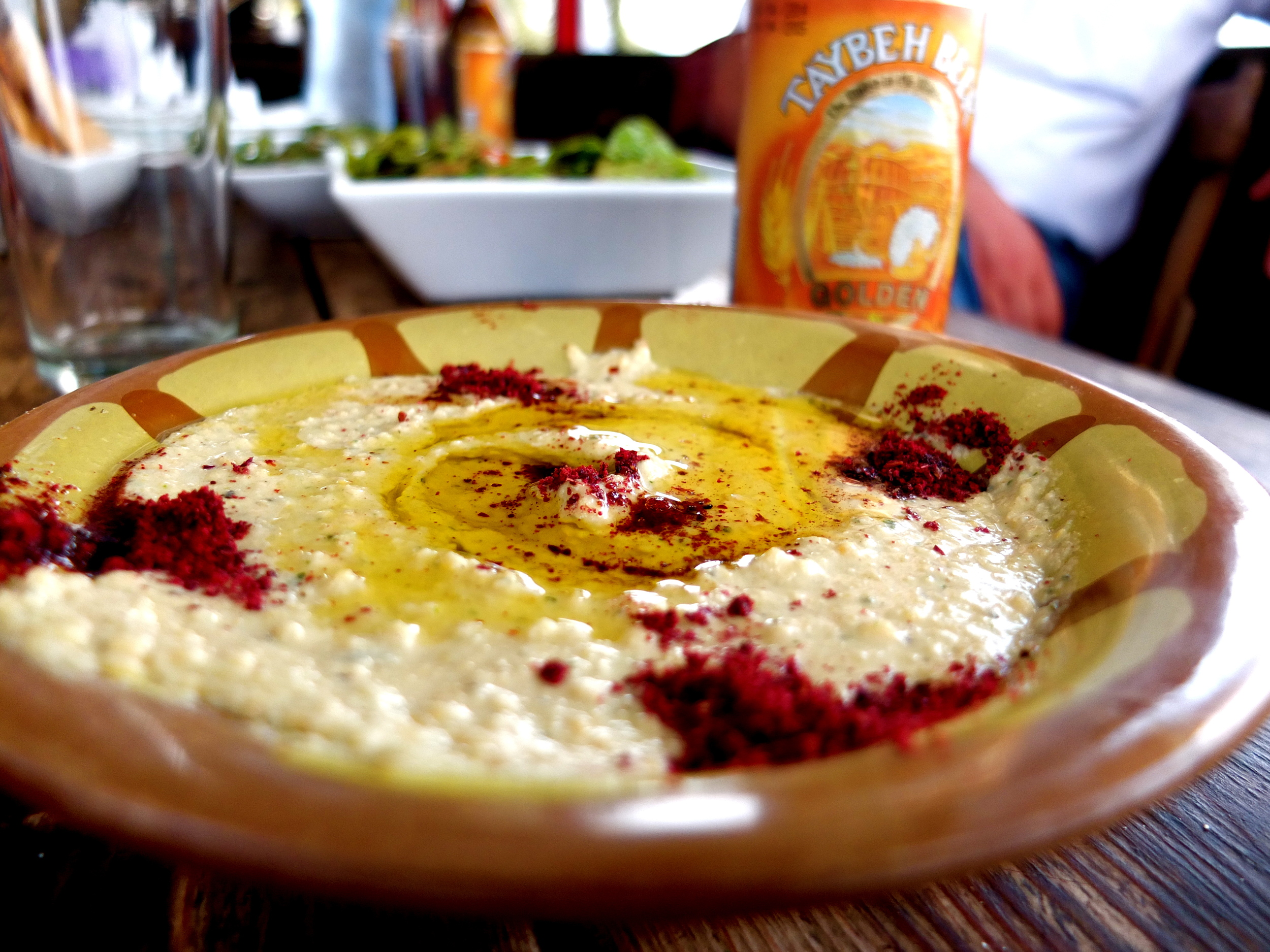 "My first meal at Hosh Jasmin included this fabulous hummus, drizzled with their     olive oil and sprinkled with tart, deep red sumac. Hummus is of course quite     contentious in this part of the world. While the image—occasionally evoked—of     Israelis and Palestinians sitting in a big circle, holding hands, and reconciling over a     big bowl of hummus is unfortunately a little too Eat, Pray, Love to be true, I do agree     with the following message I saw spray-painted on the separation wall: ""MAKE     HUMMUS NOT WAR"""