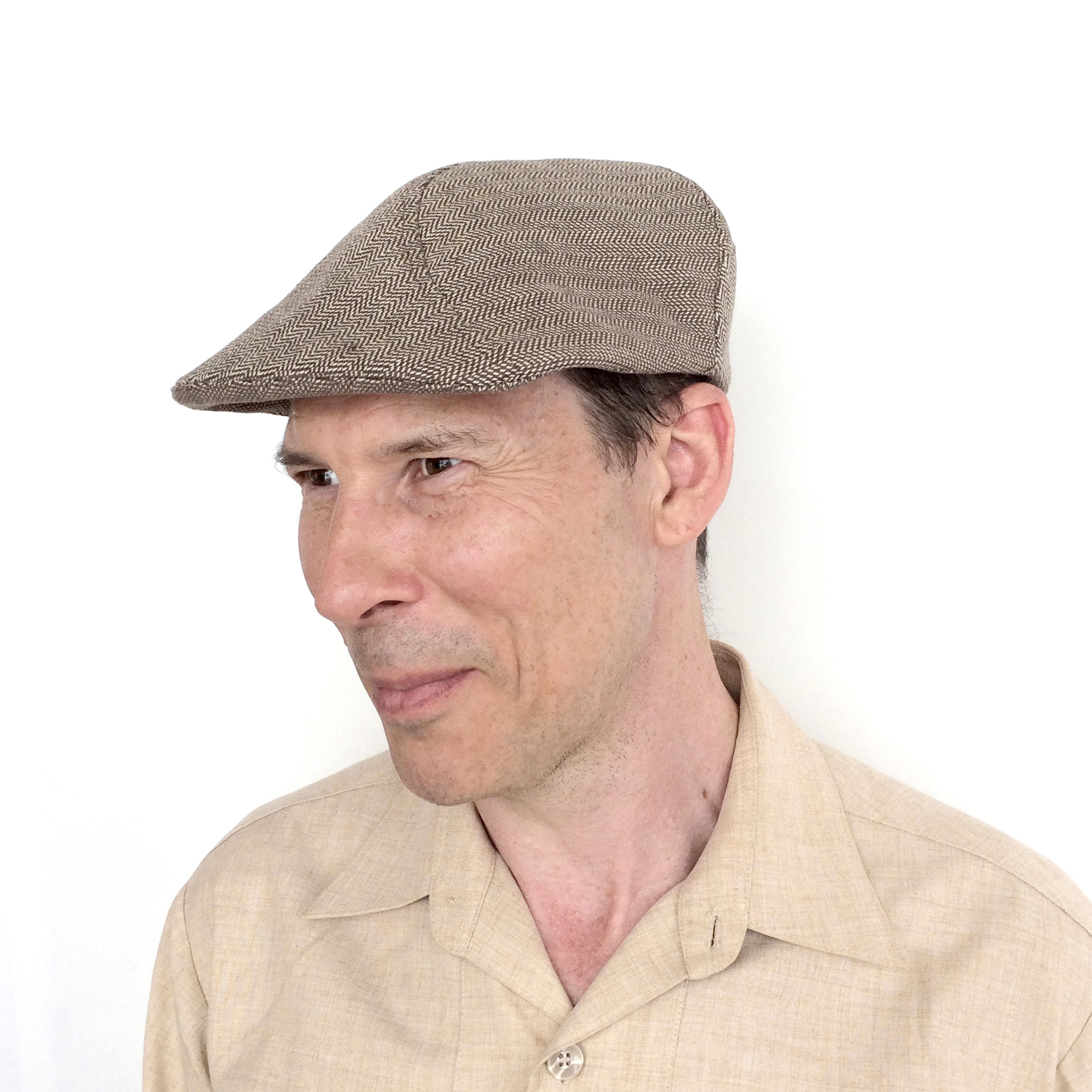 Adrian wears 'Clive' flat cap in herringbone organic cotton   buy online