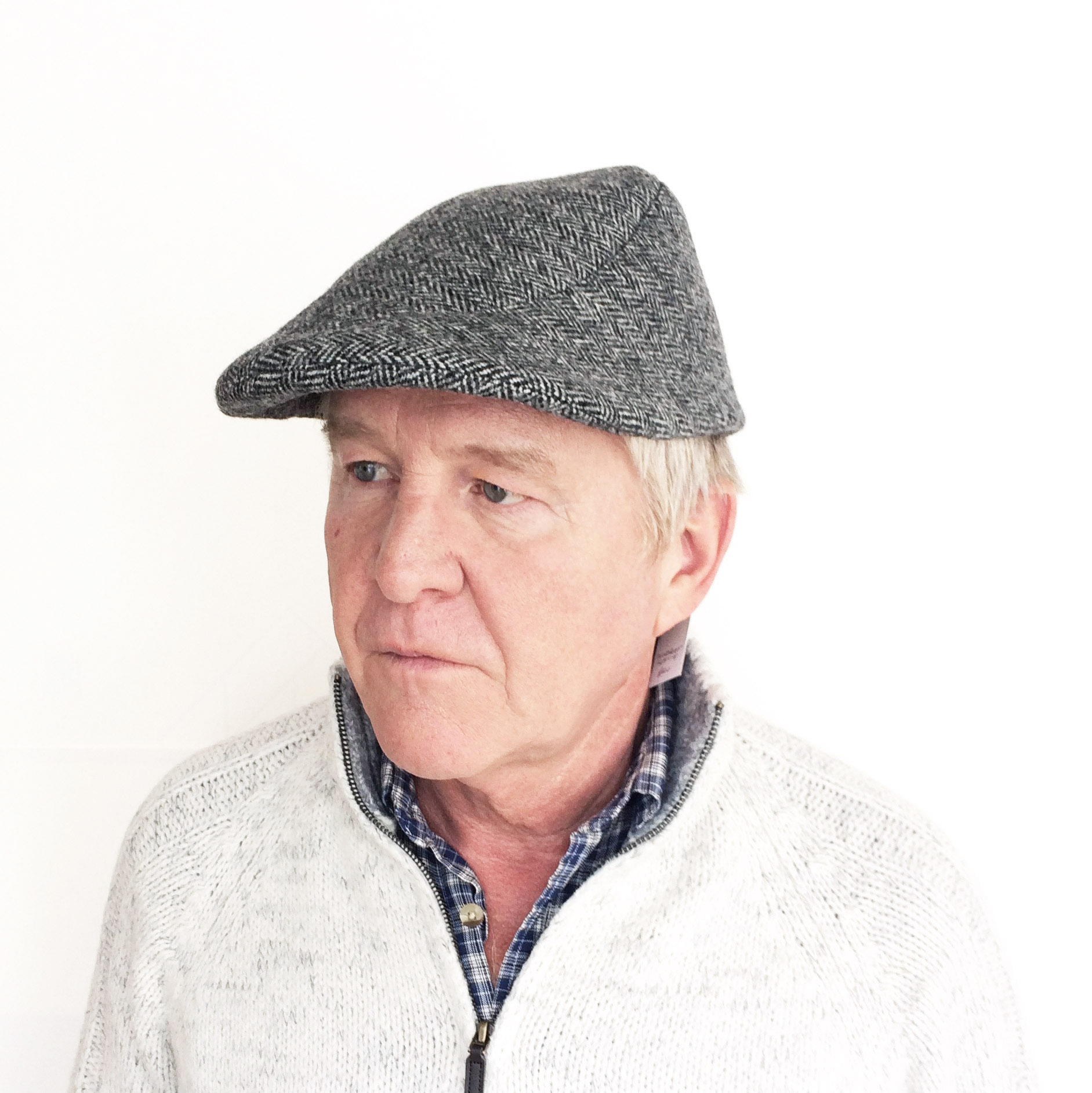 Eric wears 'Windswept Flat Cap' in grey herringbone tweed   buy online