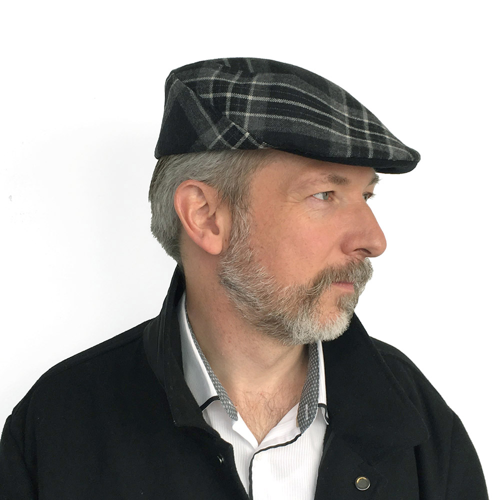 Kelvin wears 'Murray' flat cap in black/grey tartan wool