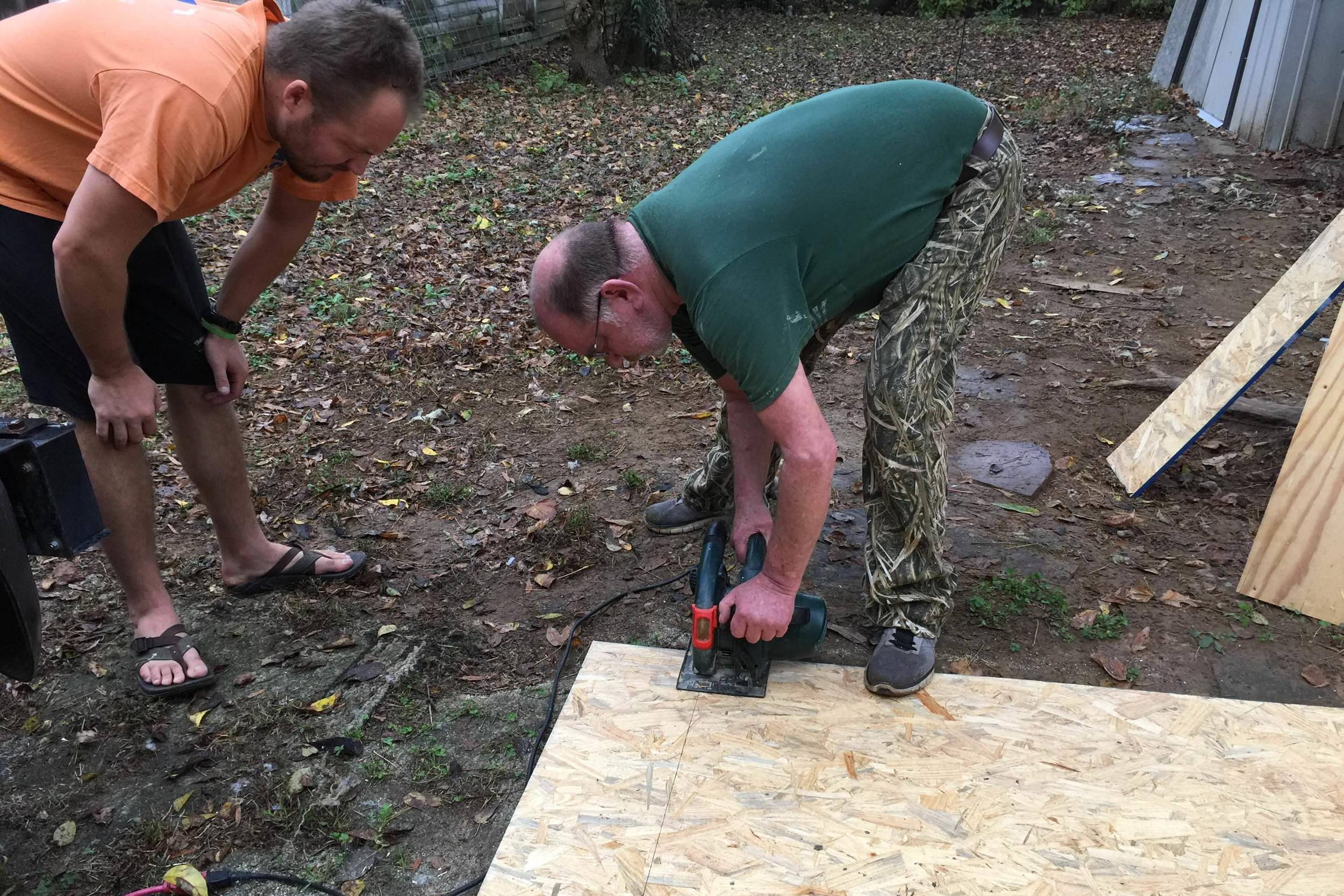 Christian let Willie show him how to cut a straight line with a skill saw.