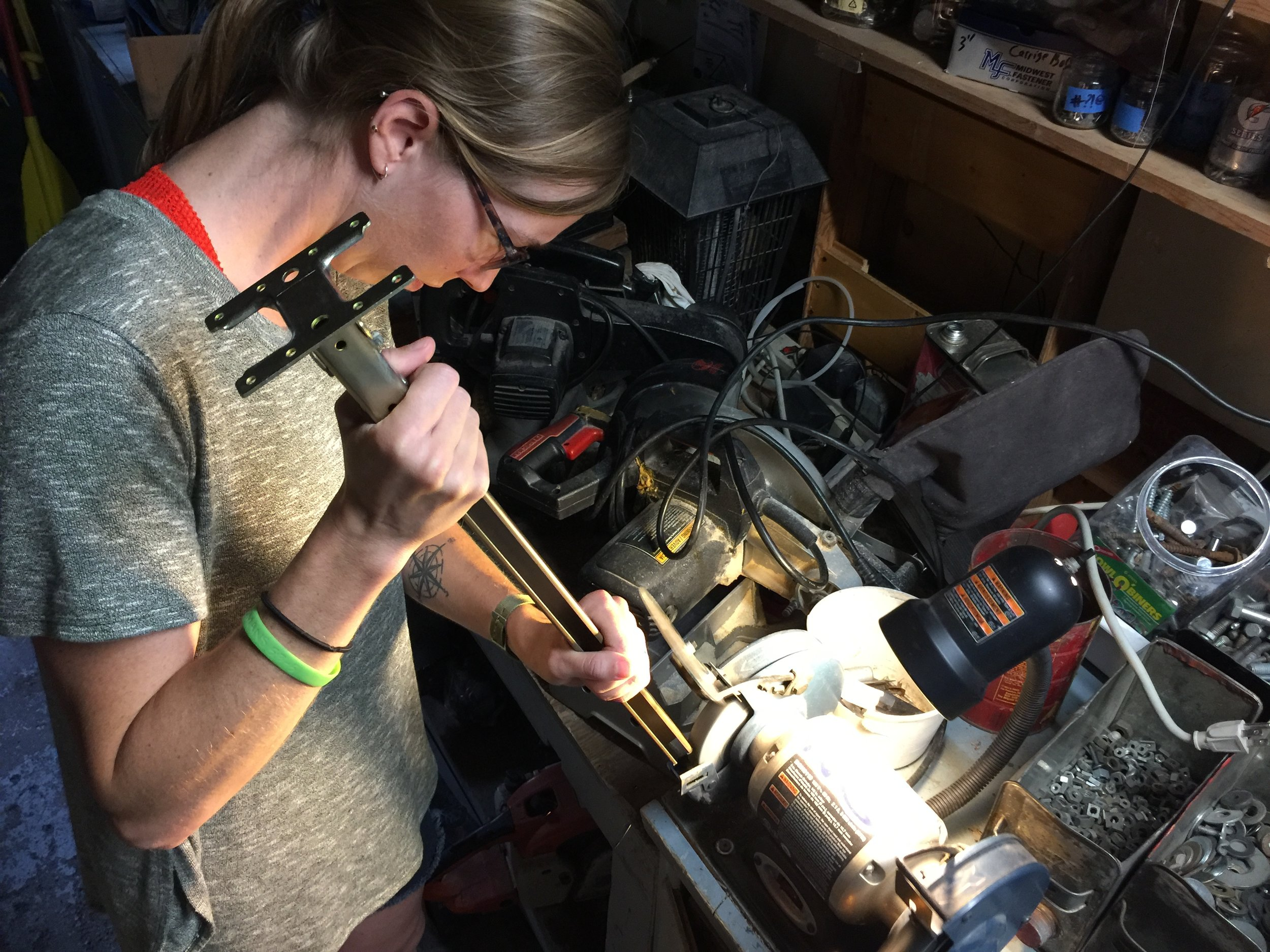 "Chels grinding away, making custom bed legs. We had to cut them to size, and Chels reminded me often that, ""Its easier to take away metal than it is to add it after its gone."" Very true. Measure, measure, measure."
