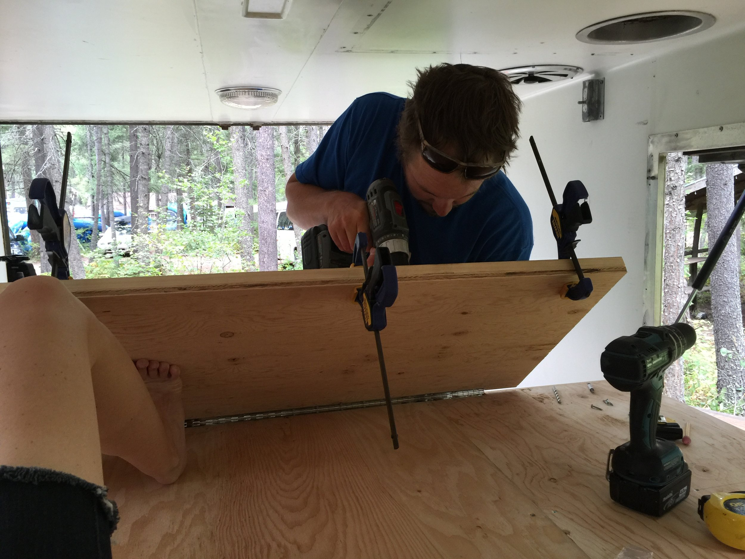 We strengthened the far lip of the fold-out foot of the bed with a 2x6, and then mounted the stow-away support legs to that. I am a large man and I can sit on that 2x6 with no bowing in the wood.