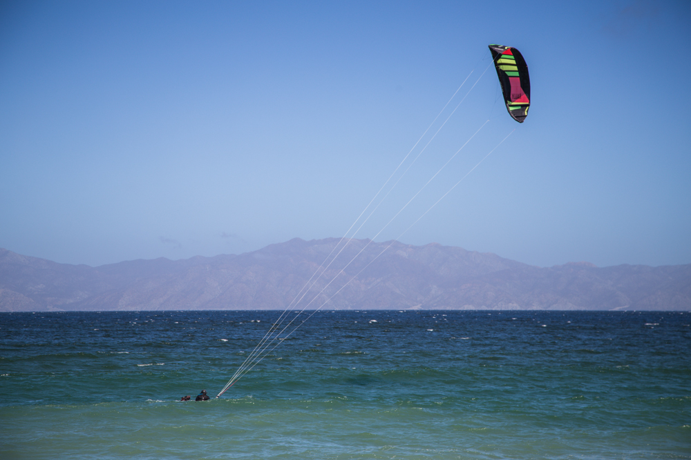 Watching a kite surfer body drag before standing up on his board.