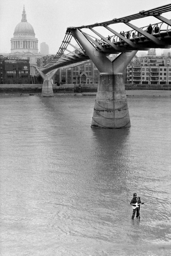Street performer in the River Thames under the Millennium Bridge, London, England. 2012