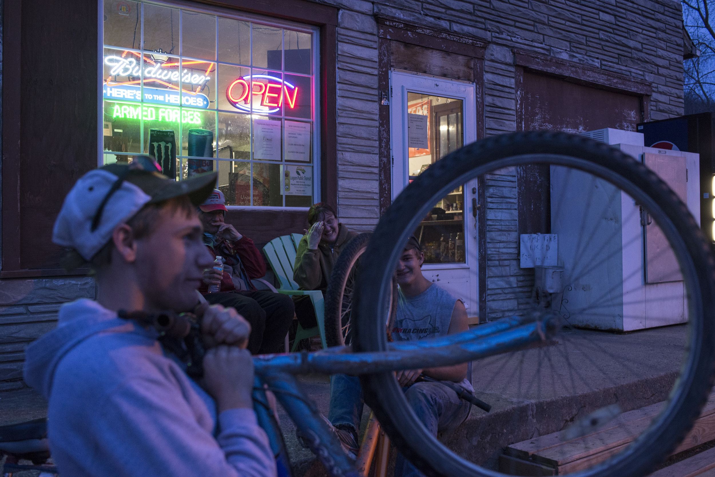 (Left to right) Jay Lambert, 17, Grover Browns, Kim Myers, and Lawrence Dotson, 17, hang out and chat in front of Mel and Kim's Carryout store. As one of only two locally owned businesses in Haydenville, Mel and Kim's also serves as a community gathering place for some residents.