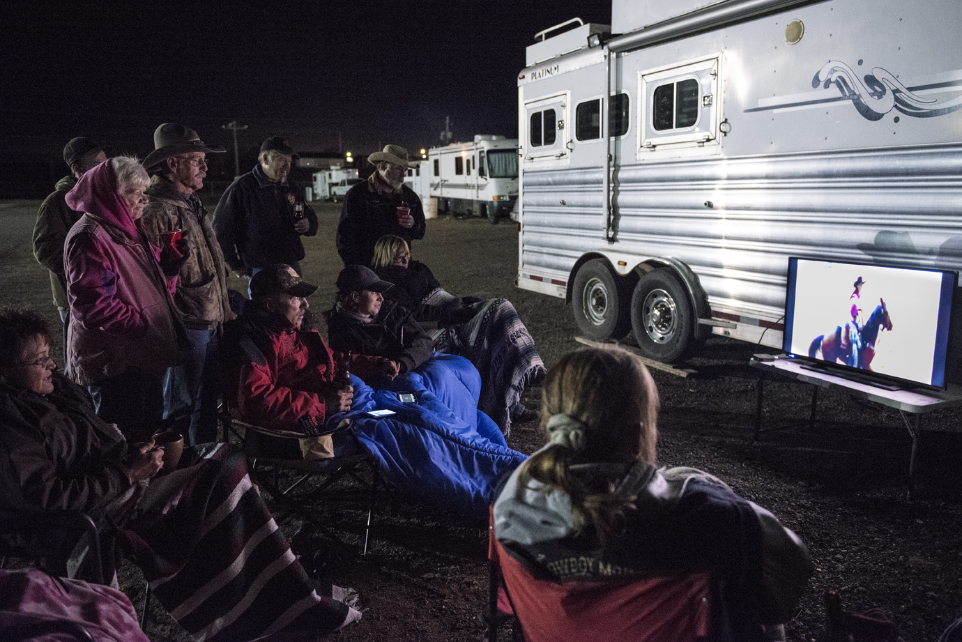 After a long day at the fun shootout, the group gathers outside one of the trailers to have a few drinks and watch the livestream of the Cowboy Mounted Shooting Association World Finals that were happening in Texas that weekend.