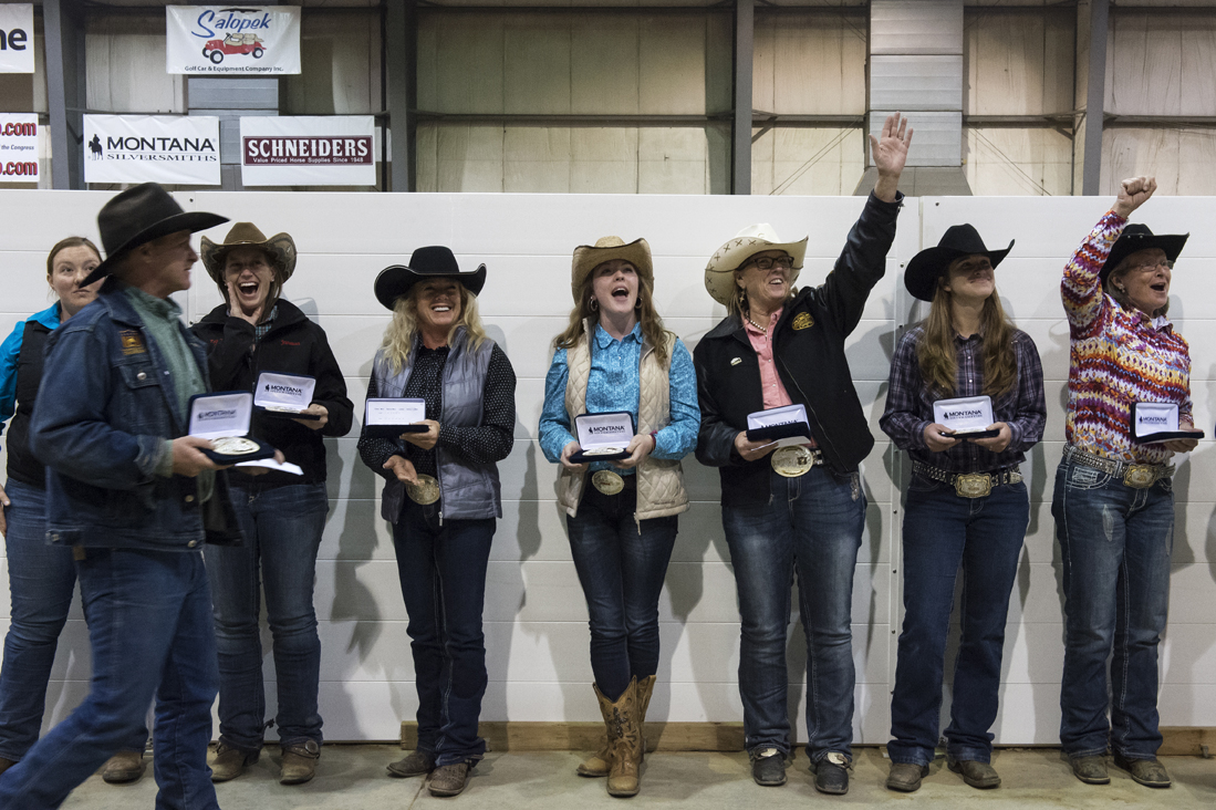 Cowgirls cheer for each other as they receive their buckles and prize money for their competition class.