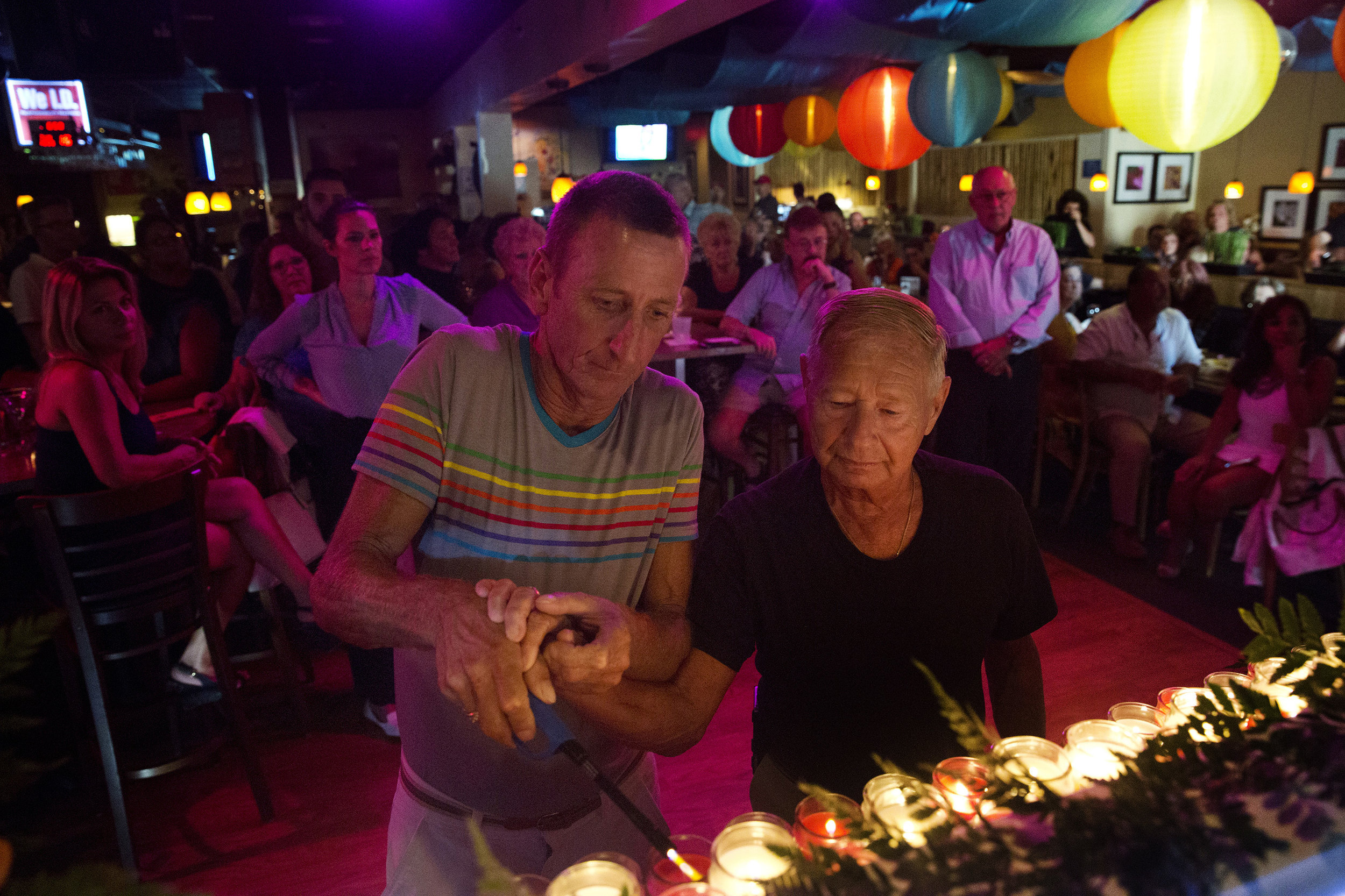 Mike Robichaud, 52, left, and Frank Cardone, 78, both of Naples, light a candle for one of the victims of the Orlando shooting at a vigil held at Bambusa Bar and Grill on June 16, 2016 in Naples, Florida. Besides lighting 49 candles to honor each of the victims, Bambusa also hosted a fundraiser auction to raise money for the survivors and the victim's families.