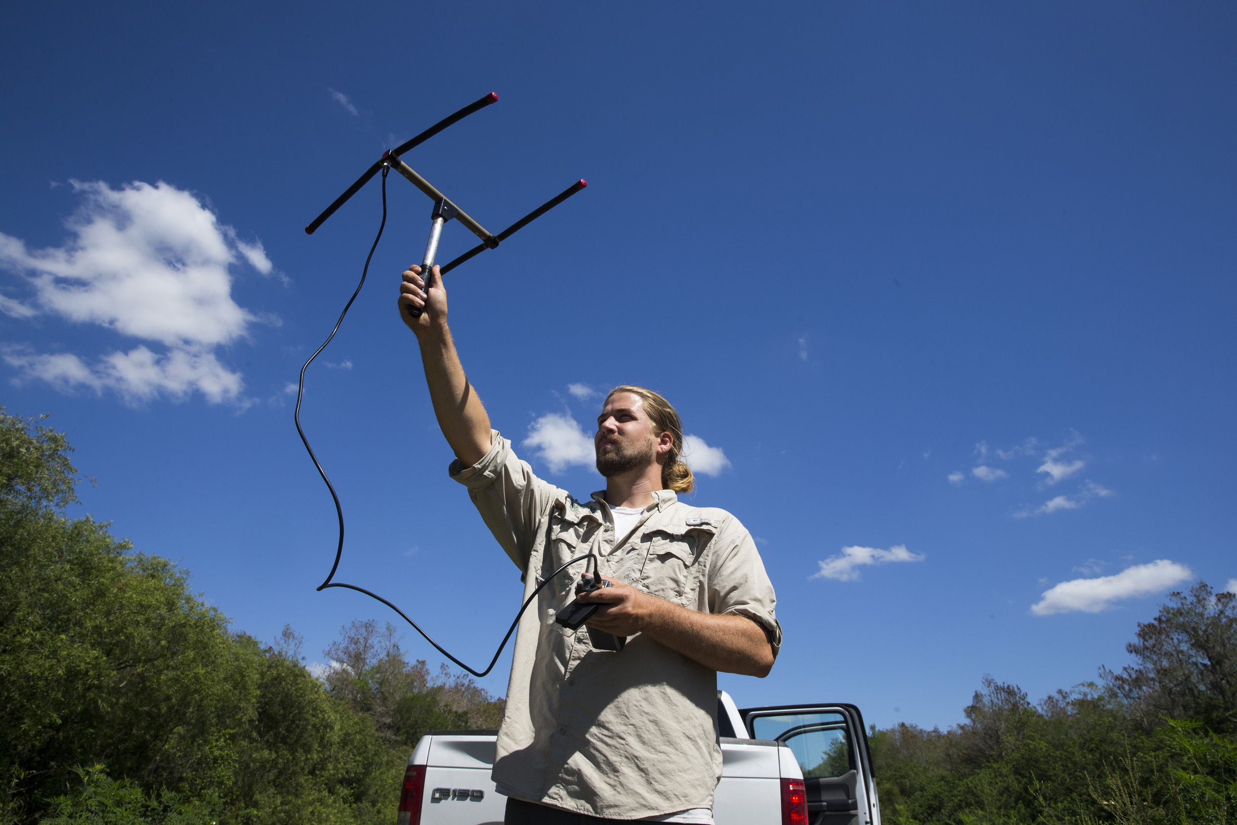 Ian Easterling, 25, a conservation associate with the Conservancy of Southwest Florida, raises an antenna to monitor Burmese pythons through radio telemetry along the edge of urban Collier Country on Tuesday, March 28, 2017.