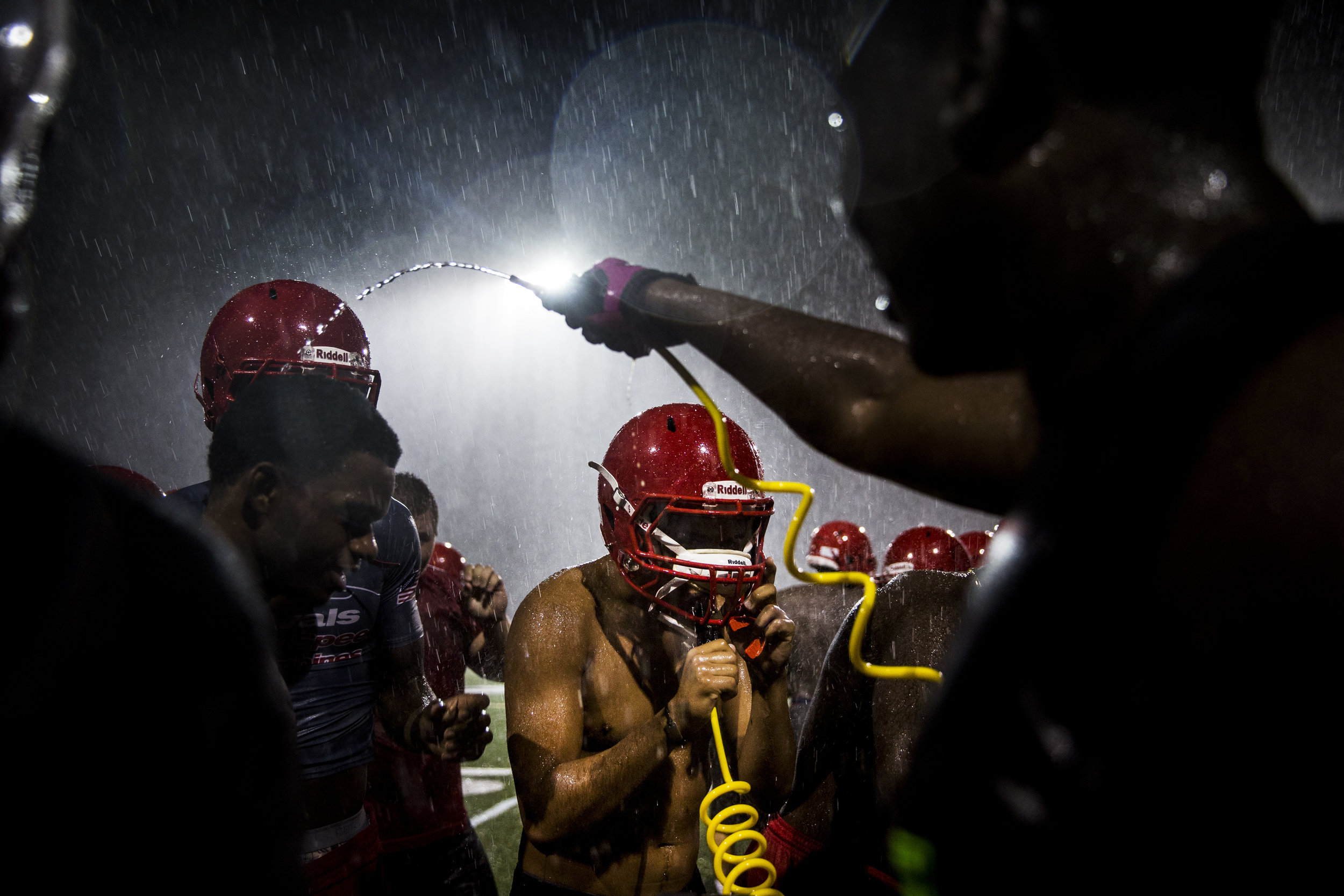 Immokalee varsity football players grab a drink during the first practice of the season at Immokalee High School on Monday, July 31, 2017.