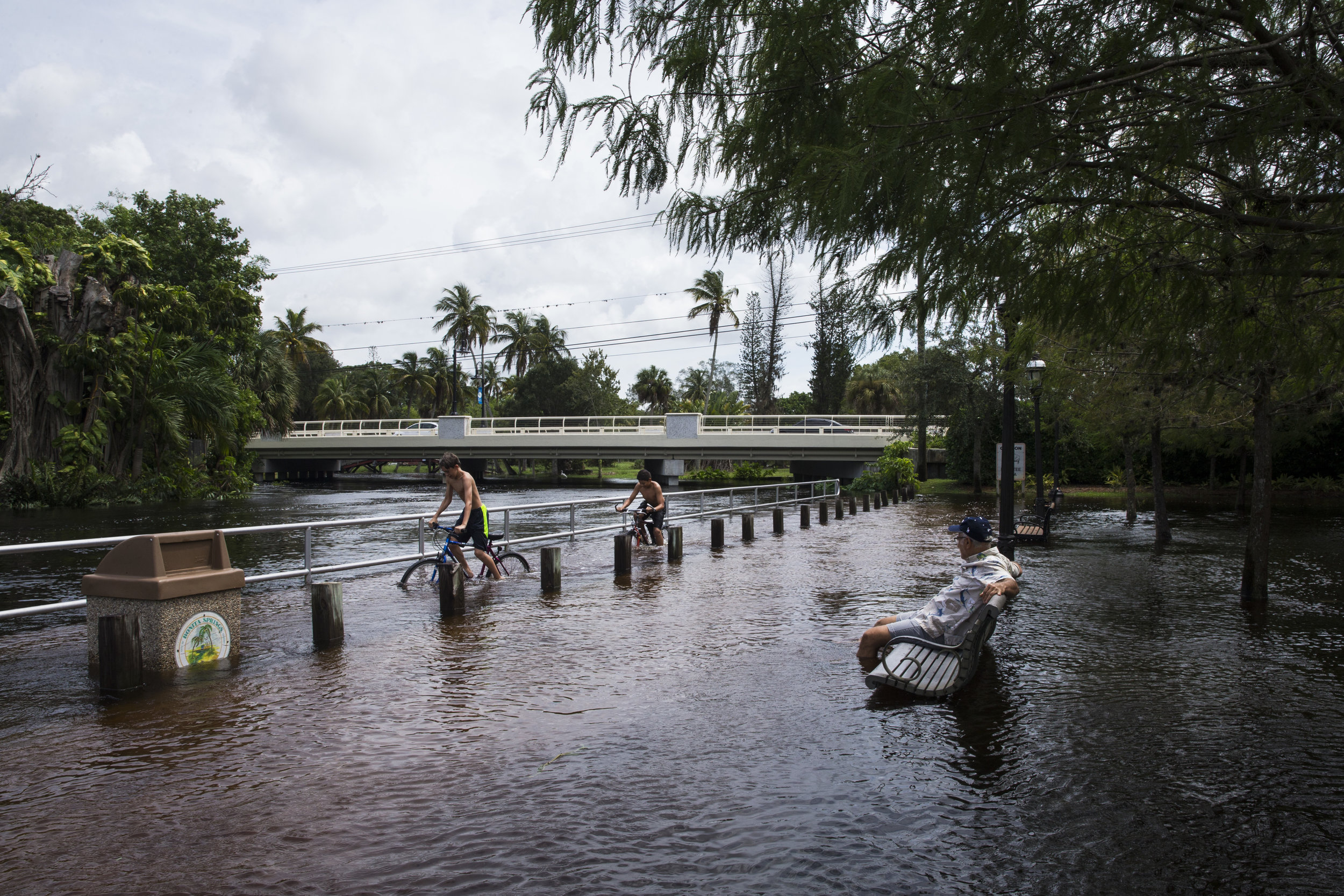 Jack Cannon, 14, from left, and Salvador Figueroa, 13, both of Bonita Springs, ride their bikes through the flooded walkway as Jerry Rabin enjoys the scene from a bench in Riverside Park in Bonita Springs on Monday, August 28, 2017.
