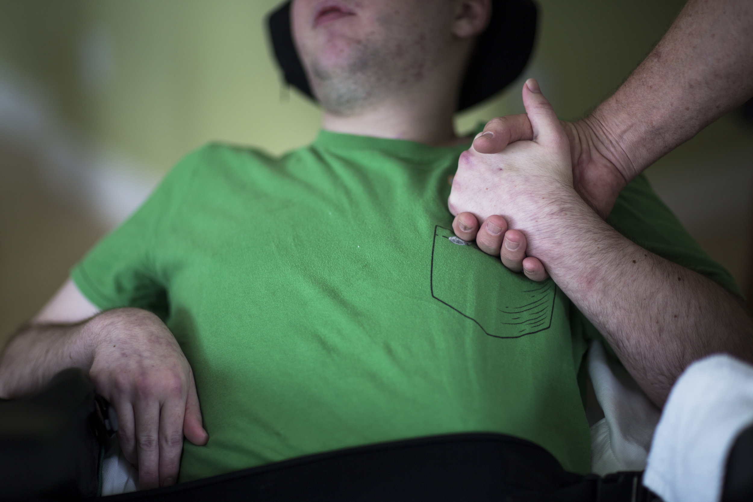 "Mitchell Reidy, 19, holds his dad's hand while sitting at home in Naples on Wednesday, Nov. 8, 2017. Reidy, who suffered a traumatic brain injury in Feb. 2017, was forced to return home after insurance rules lead to his discharge this past Monday from the Shirley Ryan AbilityLab in Chicago. ""He's going to walk again, he's going to talk again,"" Tim Reidy said. ""He's going to do all of those things."""