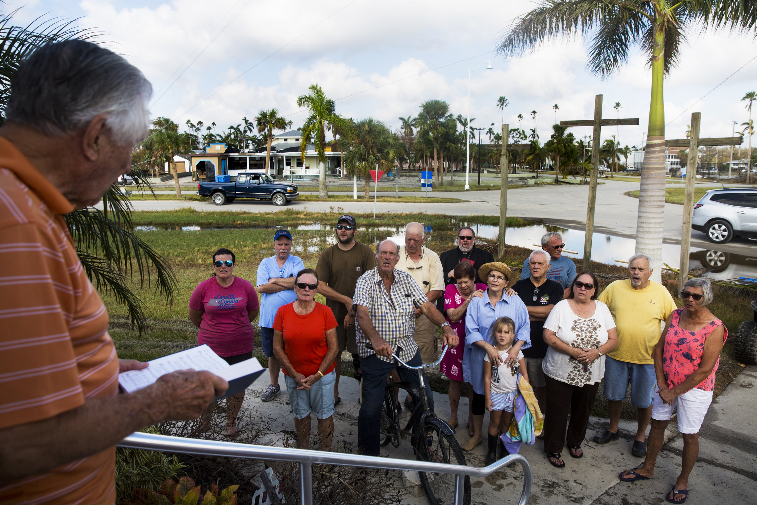 Residents of Everglades City sing songs together during a prayer service in front of Everglades Community Church on Sunday, Sept. 17, 2017.