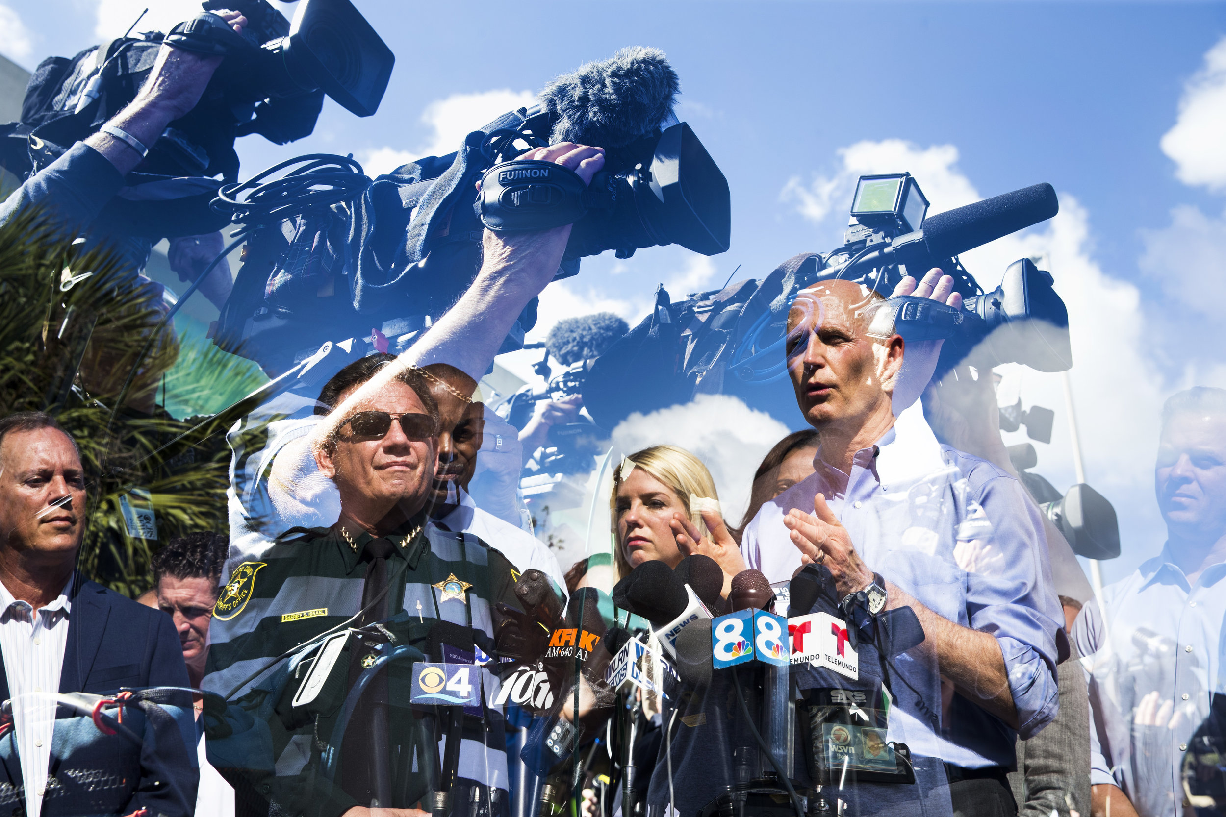 In this double exposure photo, Gov. Rick Scott addresses the press during the first media briefing on Thursday, Feb. 15, 2018 outside of Marjory Stoneman Douglas High School in Parkland, Fla., where 17 people died and several others were injured after Wednesday's mass shooting.