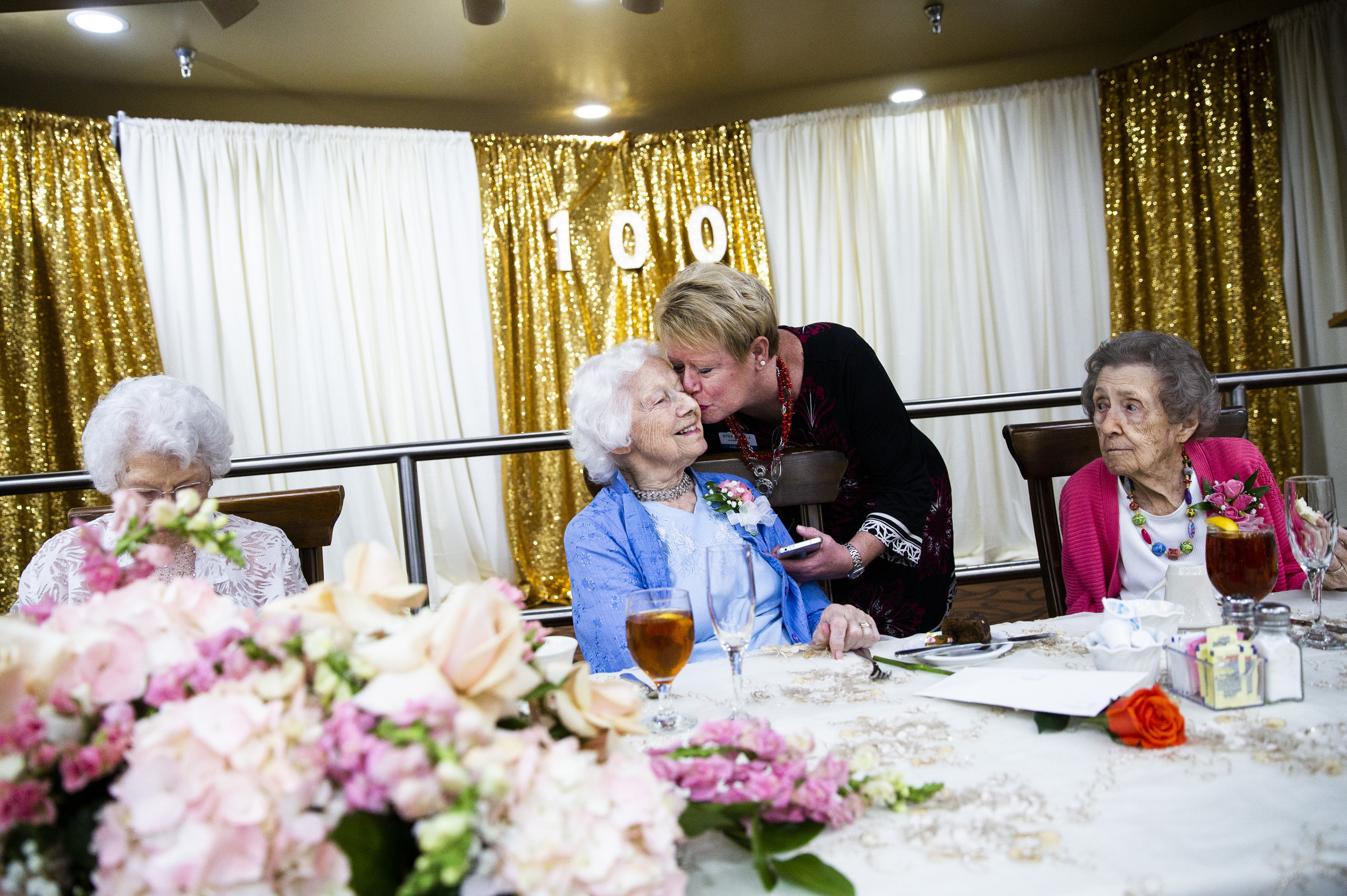 Stephanie Janke, an activities assistant, kisses Vesta Warner, 100, on the cheek to wish her a happy birthday during a celebration for the six resident centenarians at the Lely Palms Retirement Community in Naples on Wednesday, July 18, 2018.