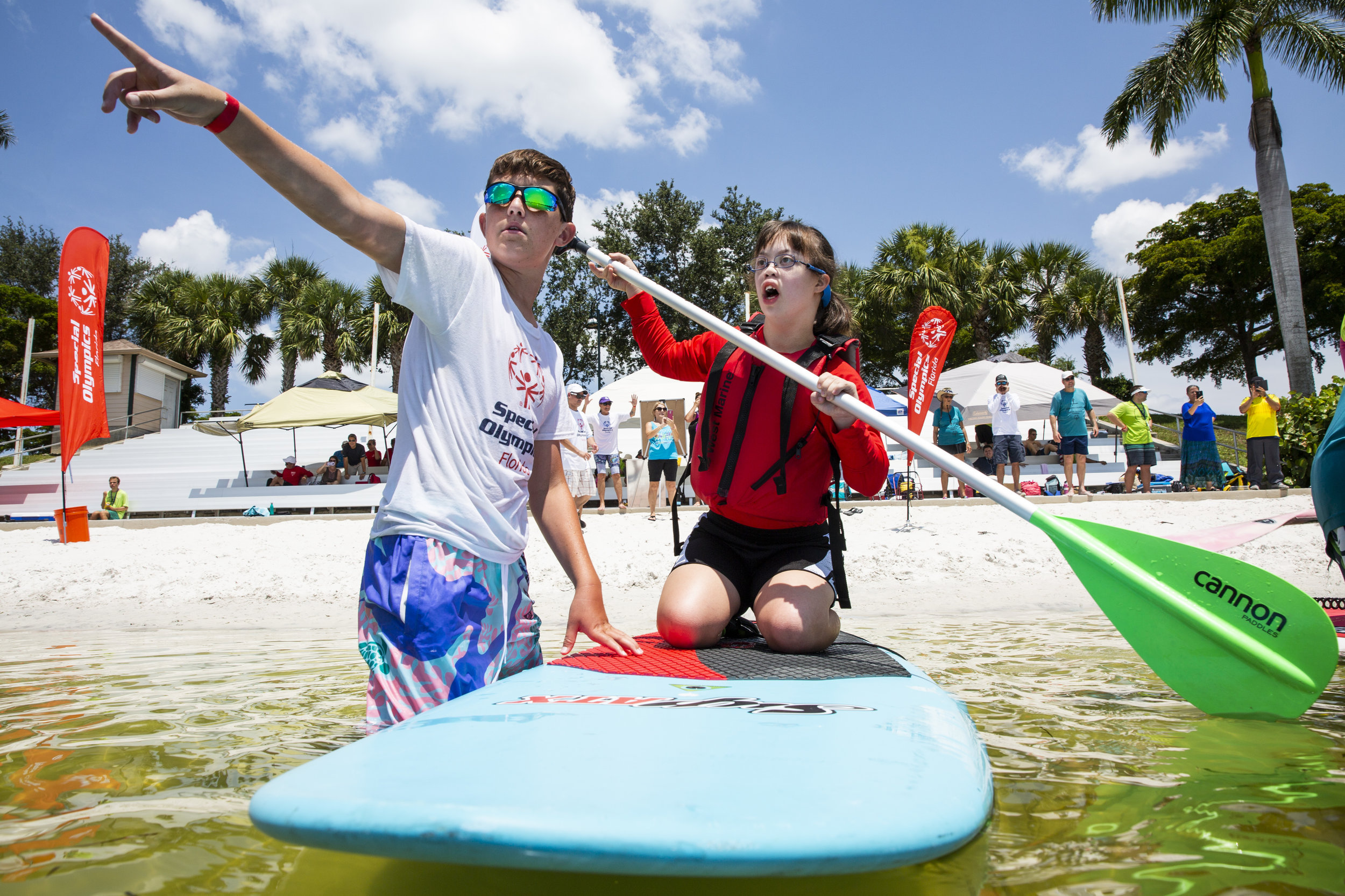 Volunteer Johnathan Konopik, 13, points out the course buoys to Natalie Pernia, 18, from Manatee County, before the start of her race during the Special Olympics Florida Area 9 Standup Paddle Competition on July 14, 2018 at Sugden Regional Park in Naples.