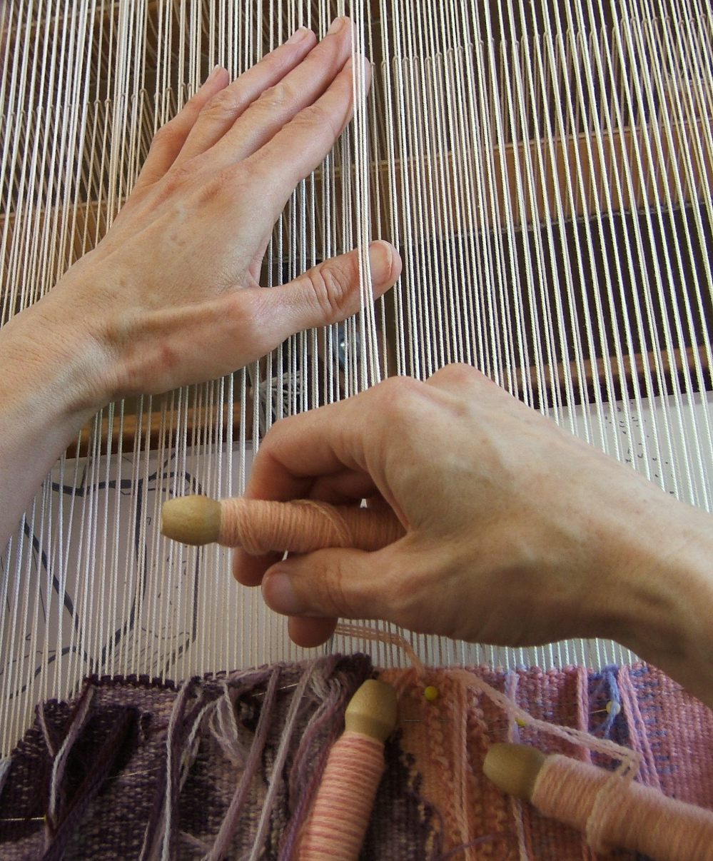 Elizabeth Buckley's hands weaving, with bobbins of crewel weight wool yarn. Photo credit: Lany Eila.