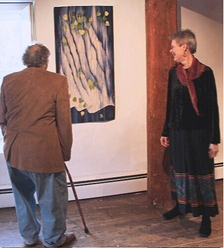 """Archie Brennan and Elizabeth Buckley in front of her tapestry, """"Dialogues Through the Veil."""" photo credit: Lisa Lomauro"""